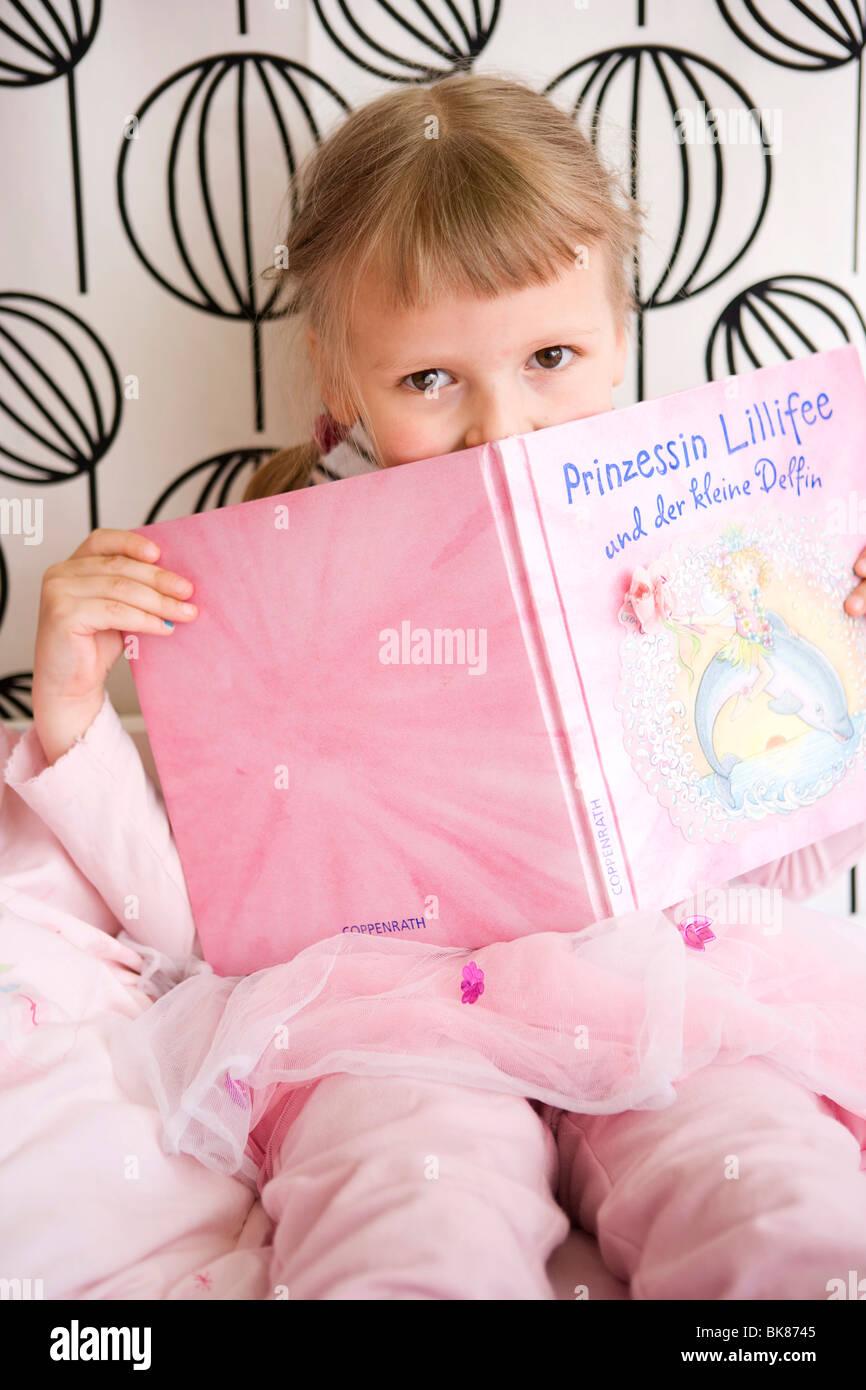 Mädchen in ihrem Schlafzimmer ein Buch hält Stockfoto