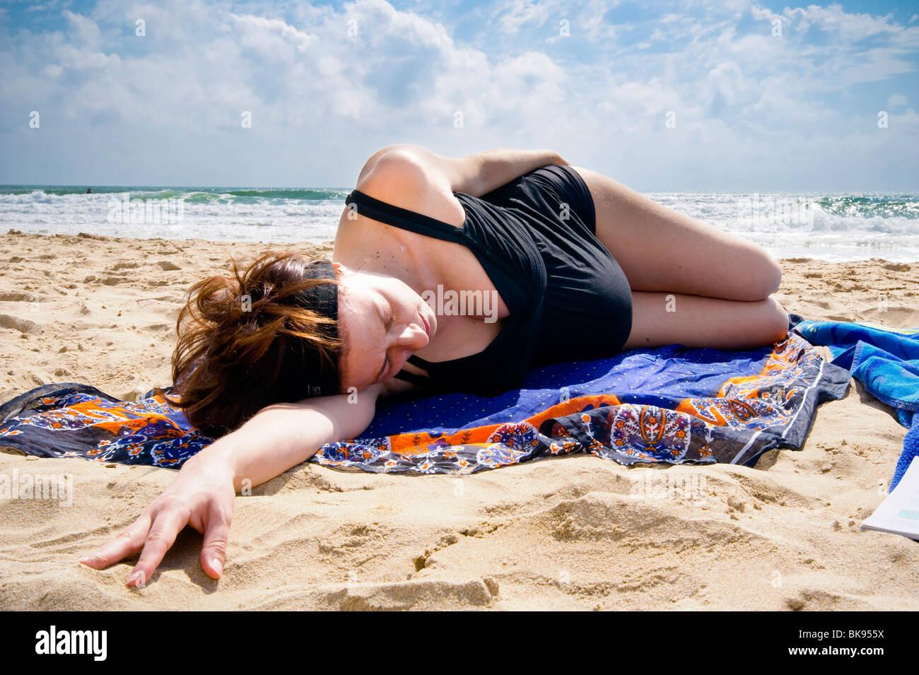 Schwangere Frau, die Festlegung auf den Strand vom Meer Stockbild