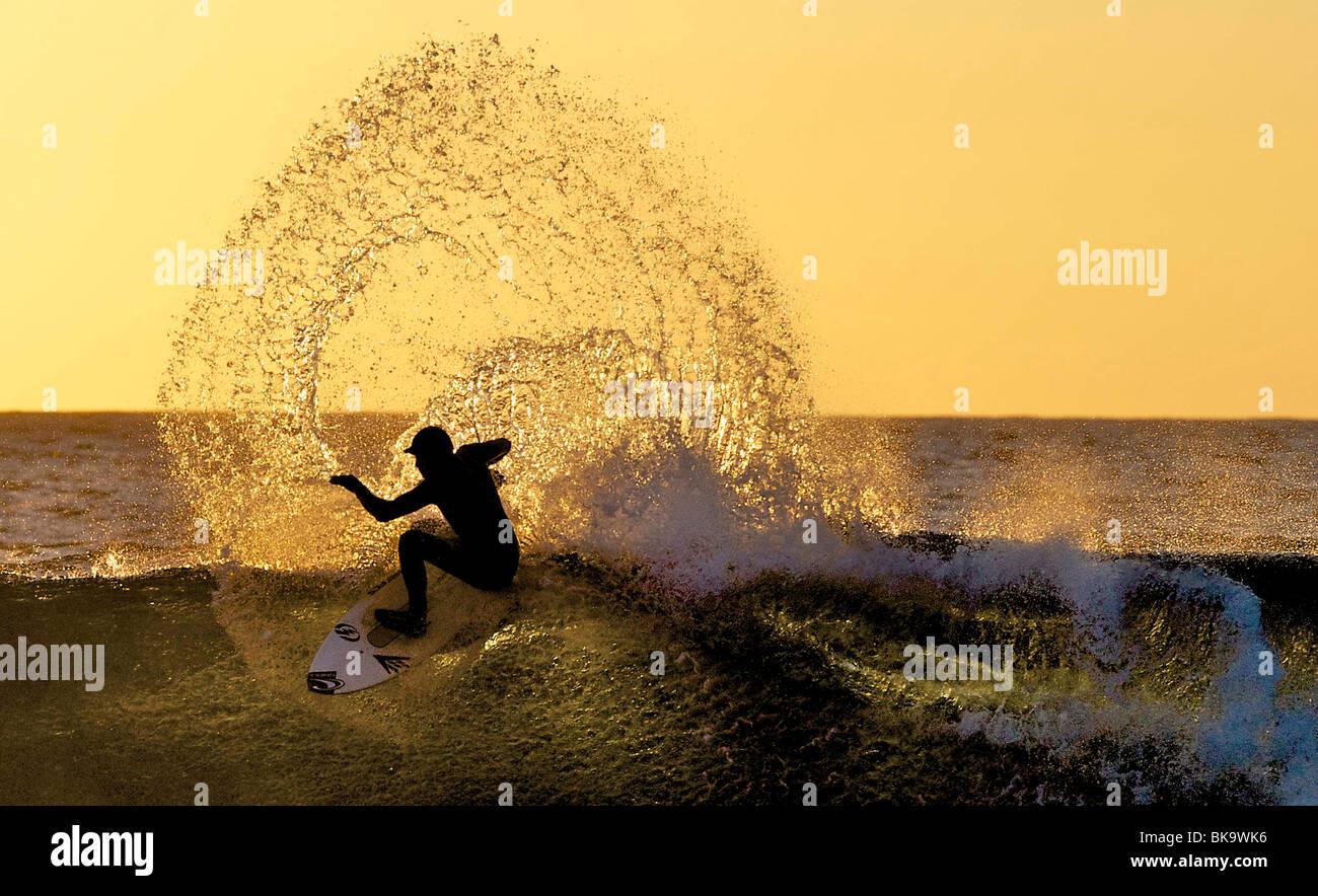 Eine Surfer ist von der Sonne am Krempen Ness in der Nähe von Thurso, Schottland Silhouette. Die Sonne geht Stockbild