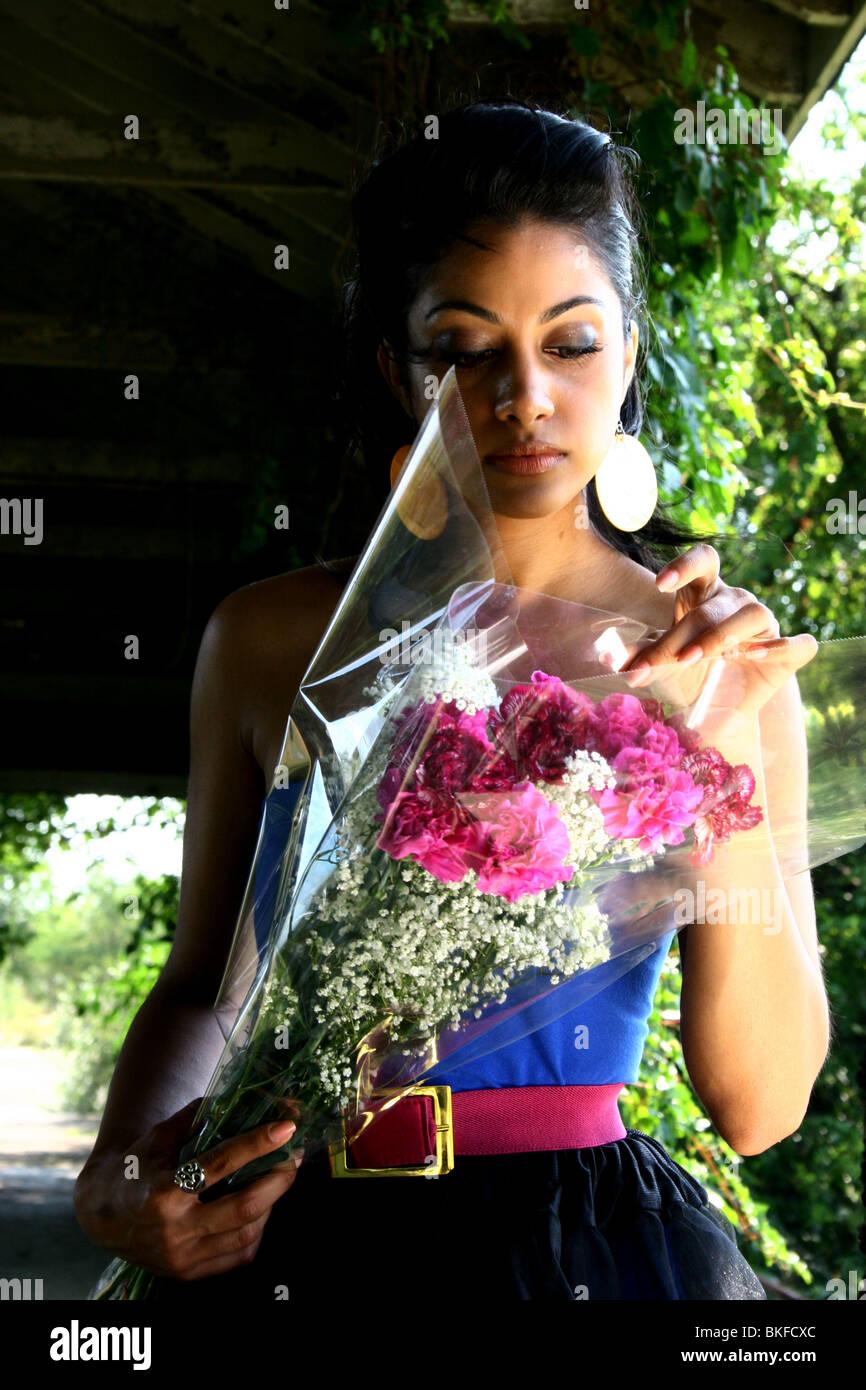 Porträt einer schönen aussehende Süd-asiatisch-amerikanische Frau mit Blumen. Stockbild