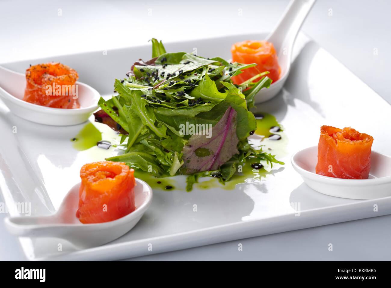 Lachs in einem weißen Teller. In der Mitte Rucola Salat. Stockbild