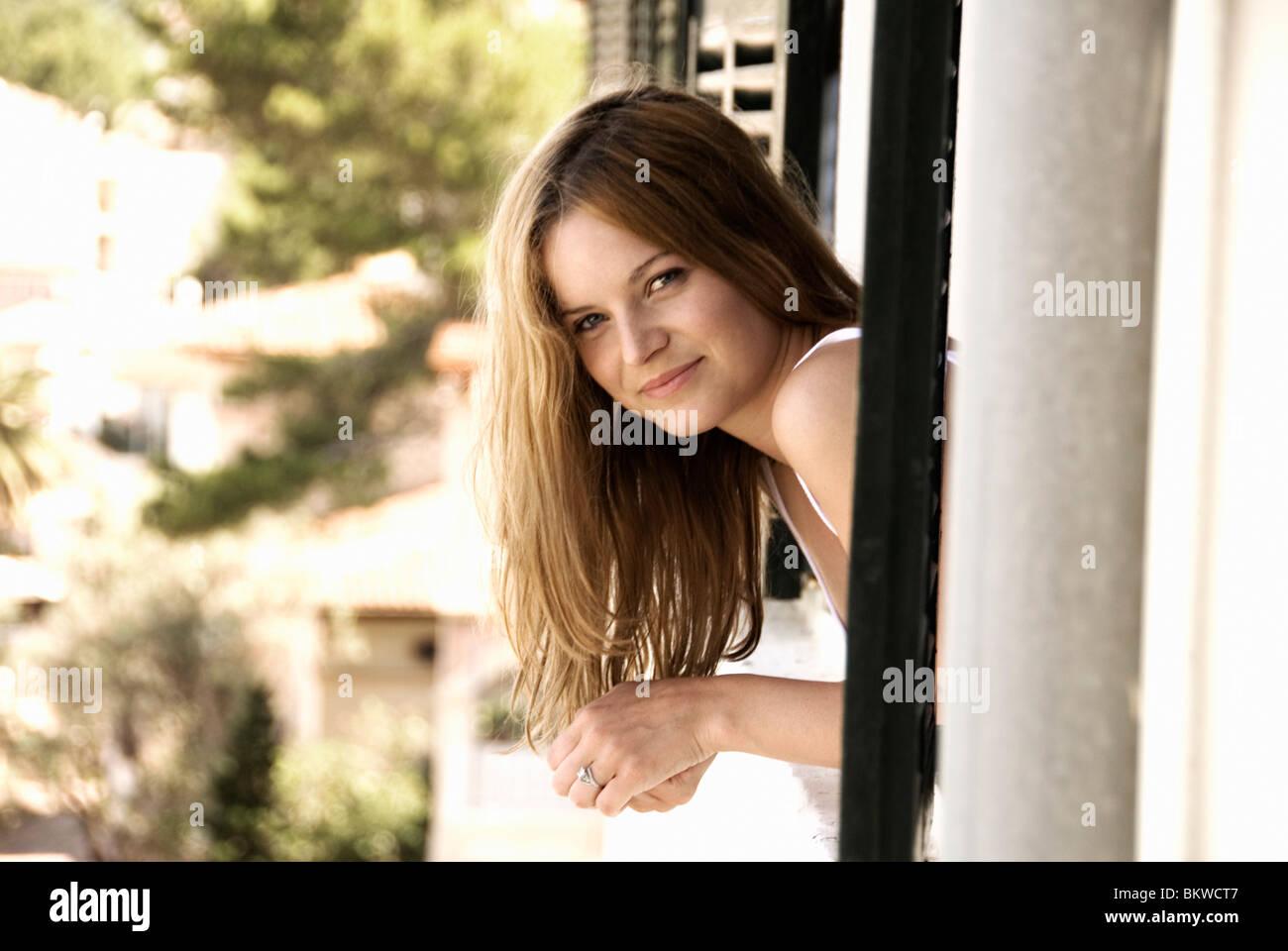 Frau im Fenster Stockbild