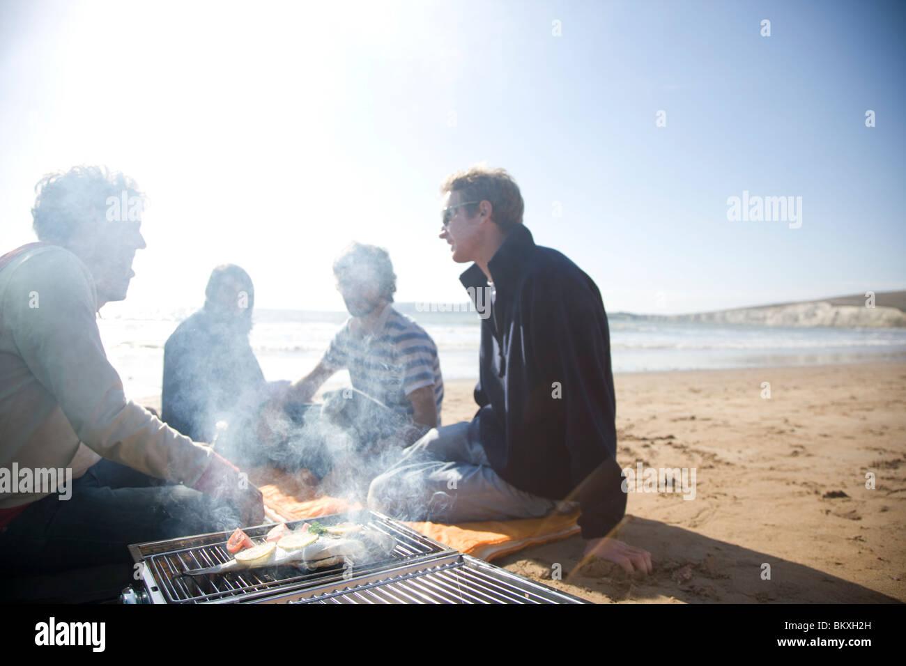 Gruppe von Freunden sitzen um ein Barbecue am Strand Stockbild
