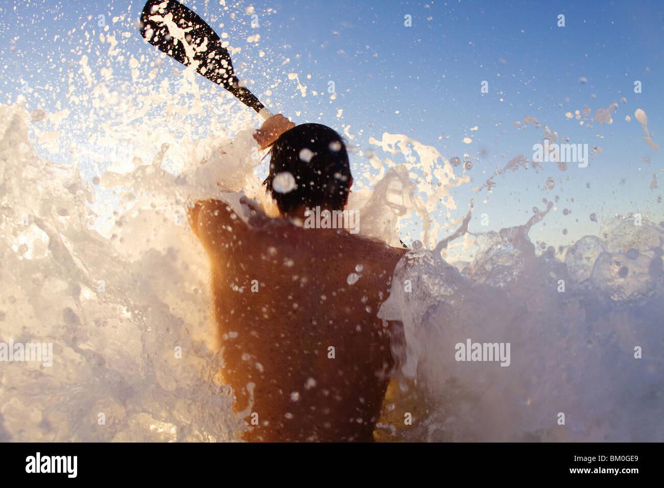 Junger Mann Kajak auf hohe Welle, Sun Coast Beach, Durban, Provinz KwaZulu-Natal, Südafrika Stockfoto