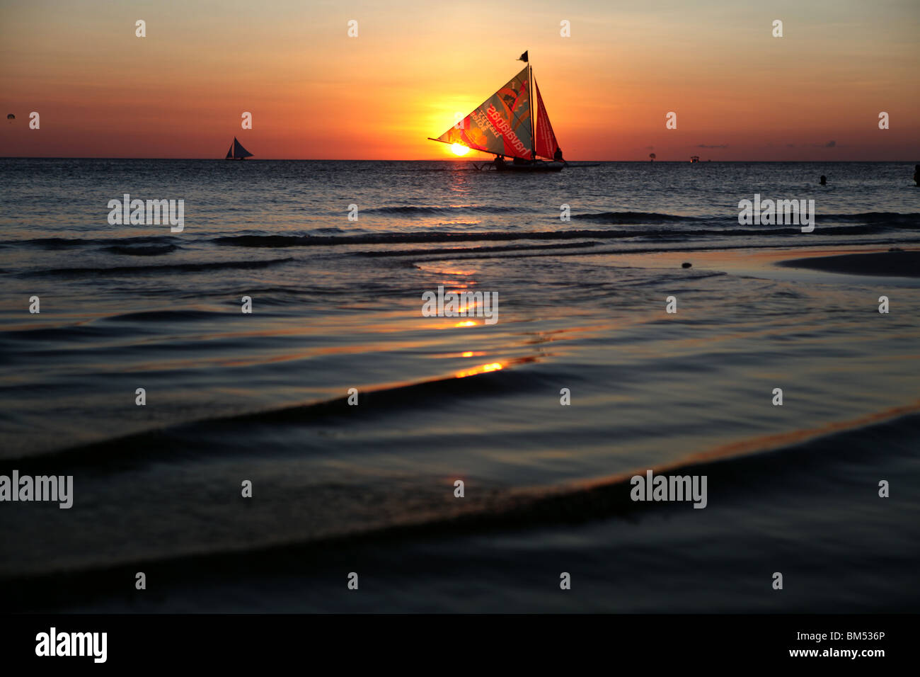 Ein Segelboot übergibt den Sonnenuntergang am White Beach, Boracay, das wohl bekannteste Reiseziel auf den Stockbild