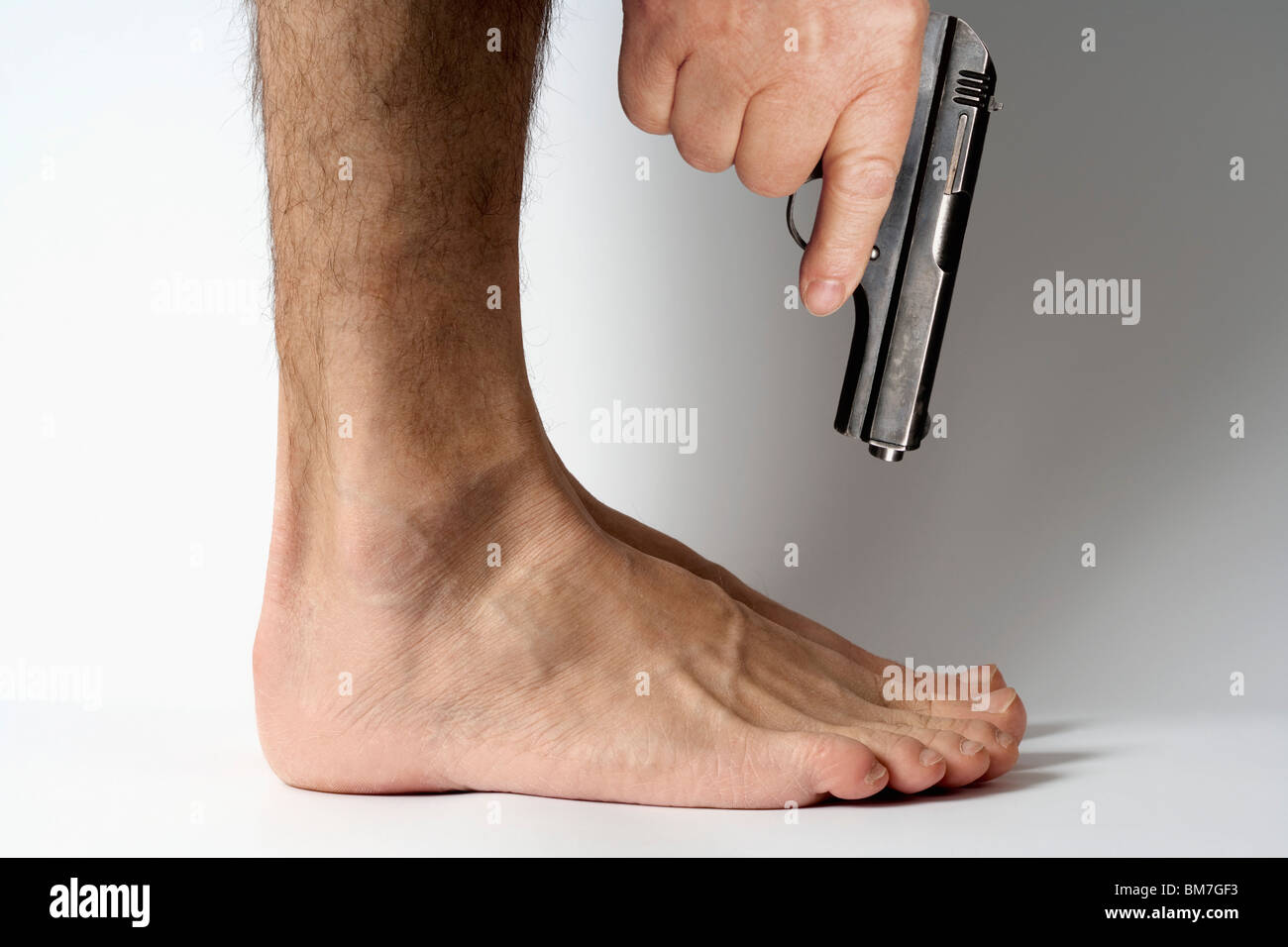 Selbst in den Fuß schießen Stockbild