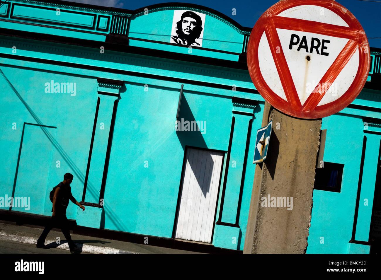 Ein Mann geht durch ein helles blaues Gebäude geschmückt mit einem Bild von Ernesto Che Guevara in Baracoa, Stockbild