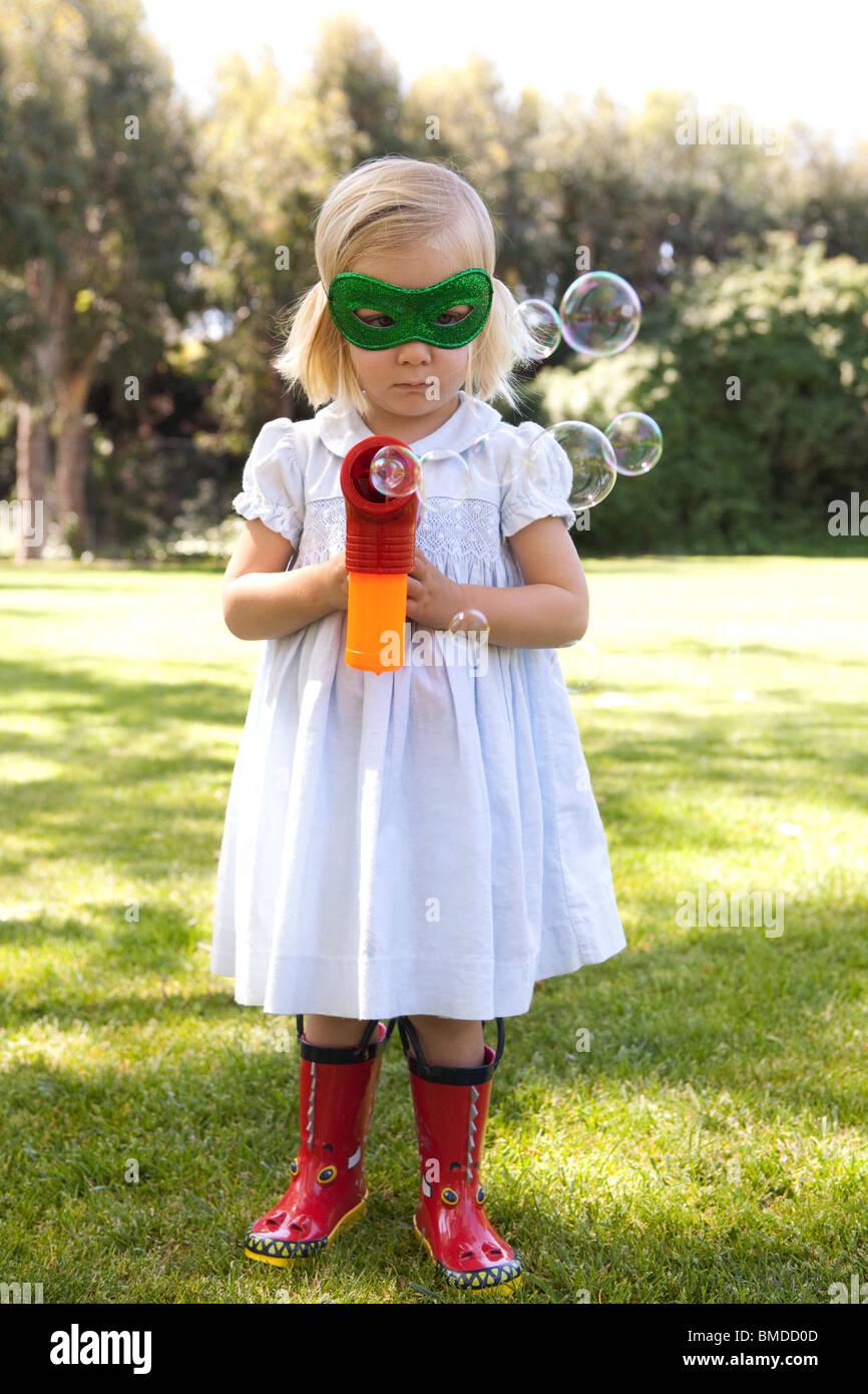 Junges Mädchen mit Bubble Gun in Maske Stockbild