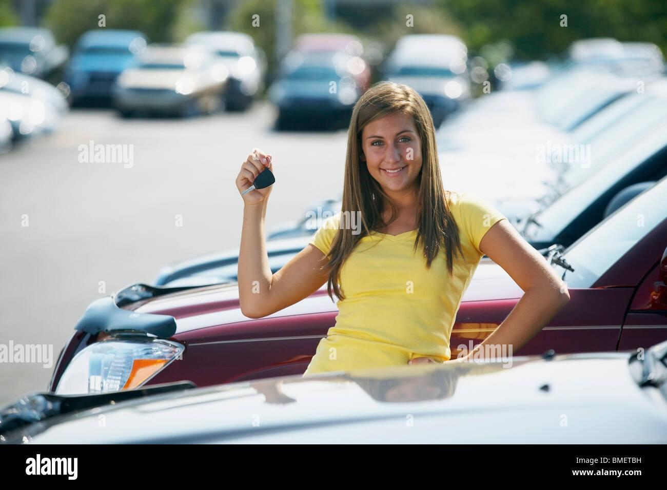 Eine junge Frau mit Tasten, um ein Fahrzeug In einem Autohaus Stockbild