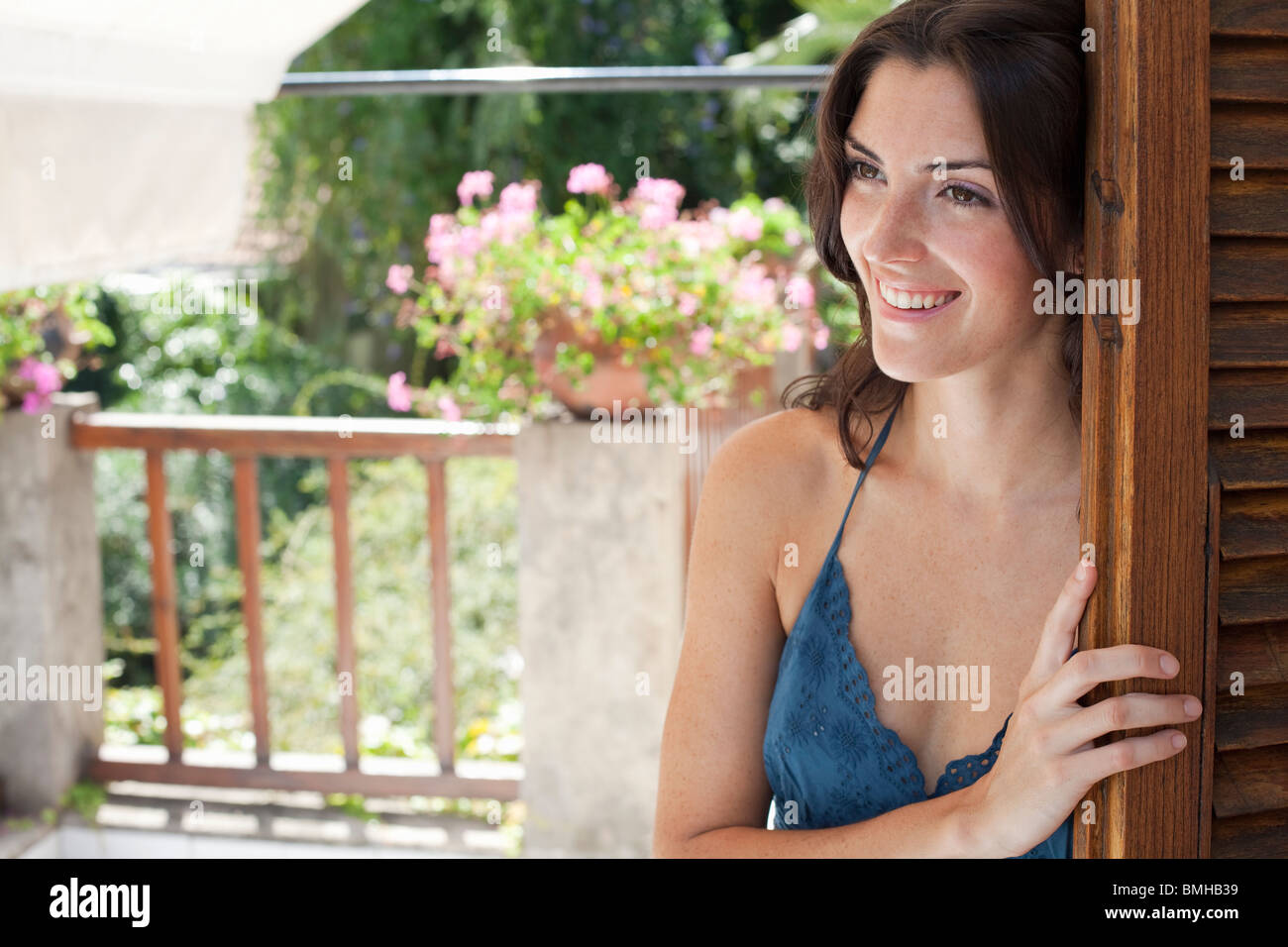 Frau Jalousien zur Terrasse öffnen Stockbild