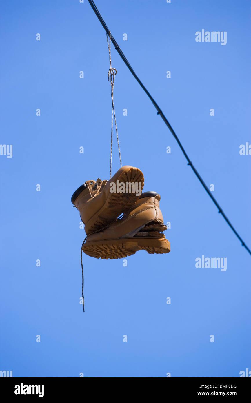 Paar Stiefel hängen über Elektrokabel mit Himmel Hintergrund, Drogen-und Medikamentenmissbrauch, Drogen, Stockbild