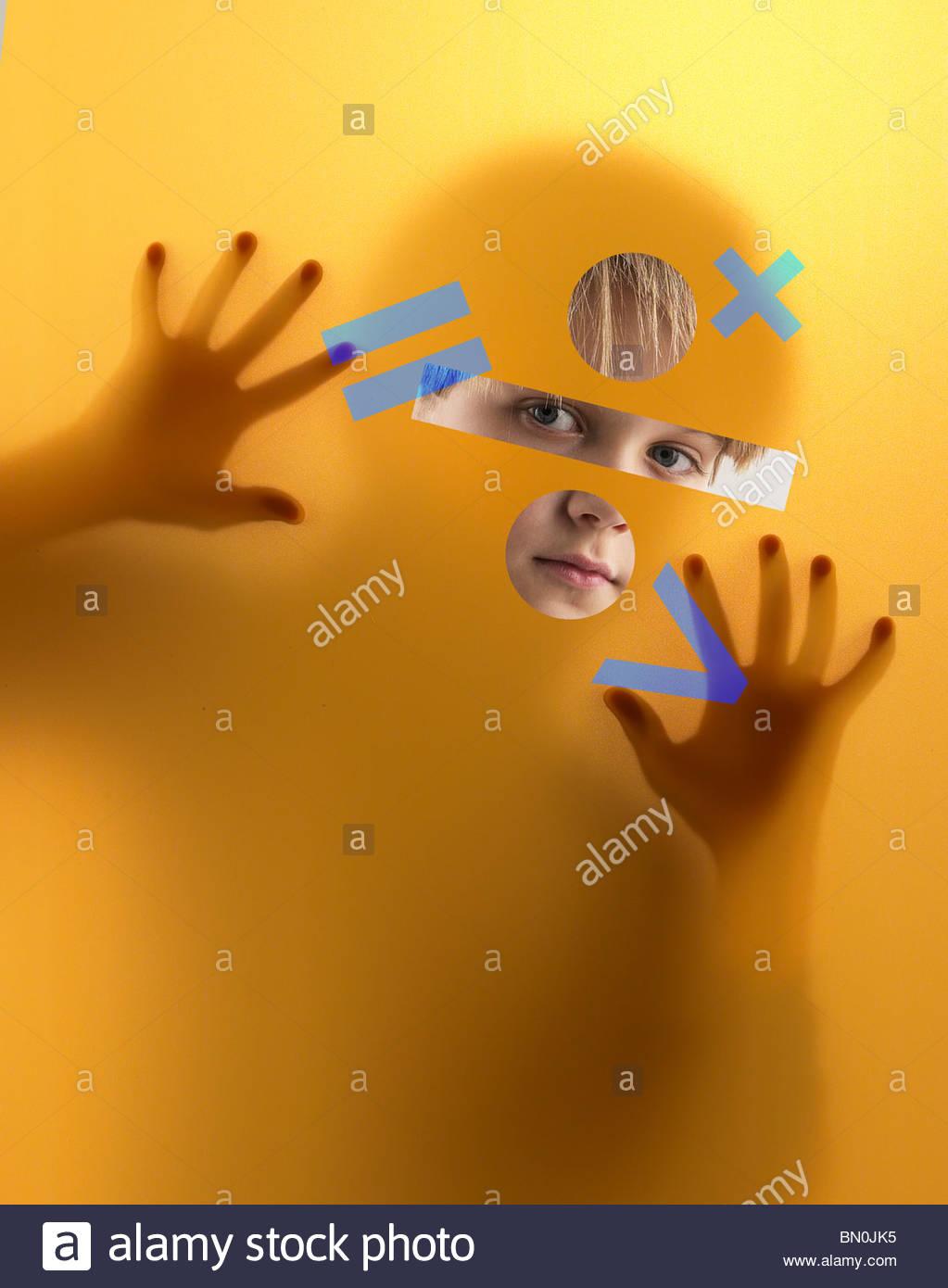 Ein Junge blickt durch ein Sieb in Mathematik Symbole abgedeckt Stockbild