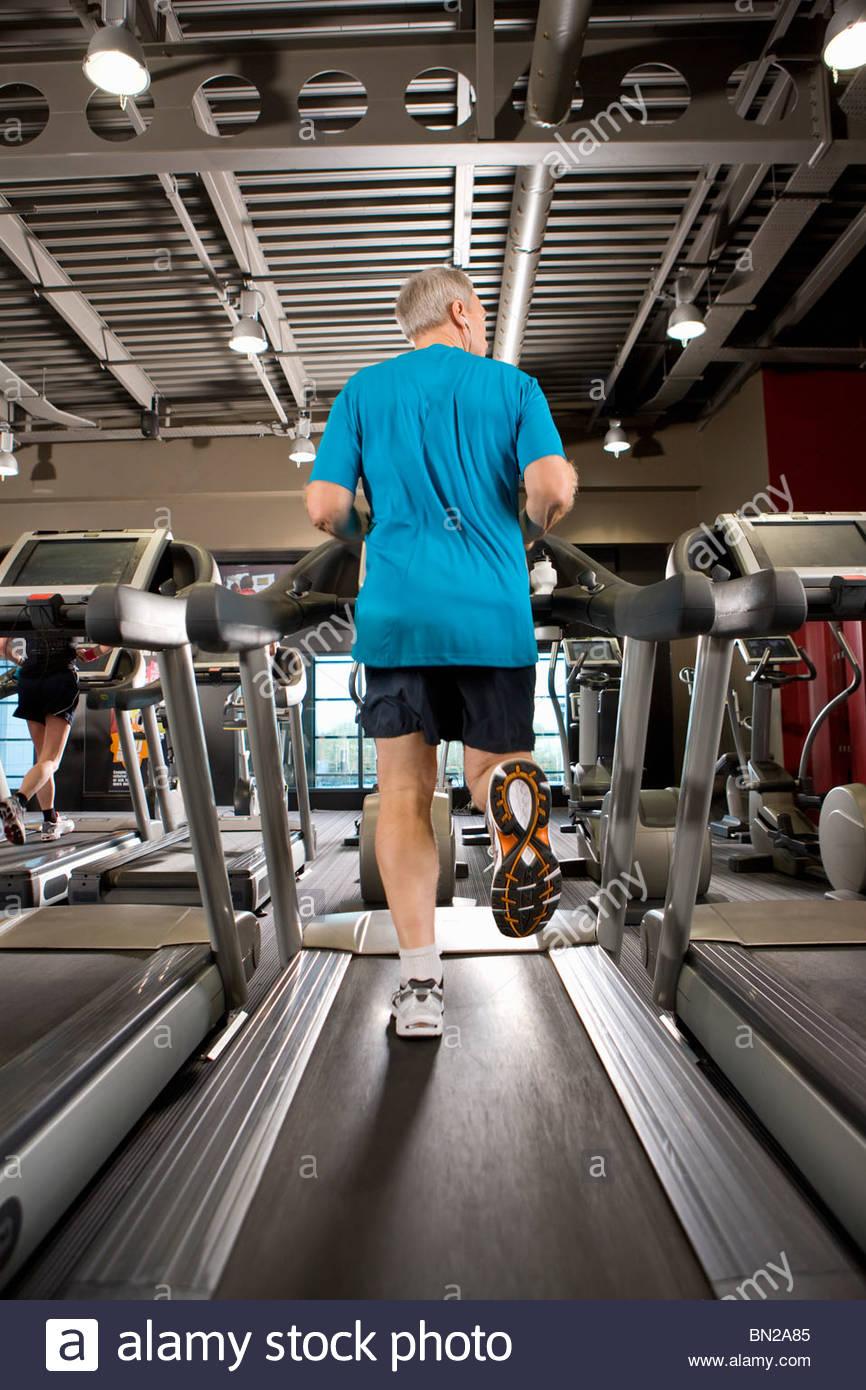 Mann läuft auf Laufband im Fitnessstudio Stockbild