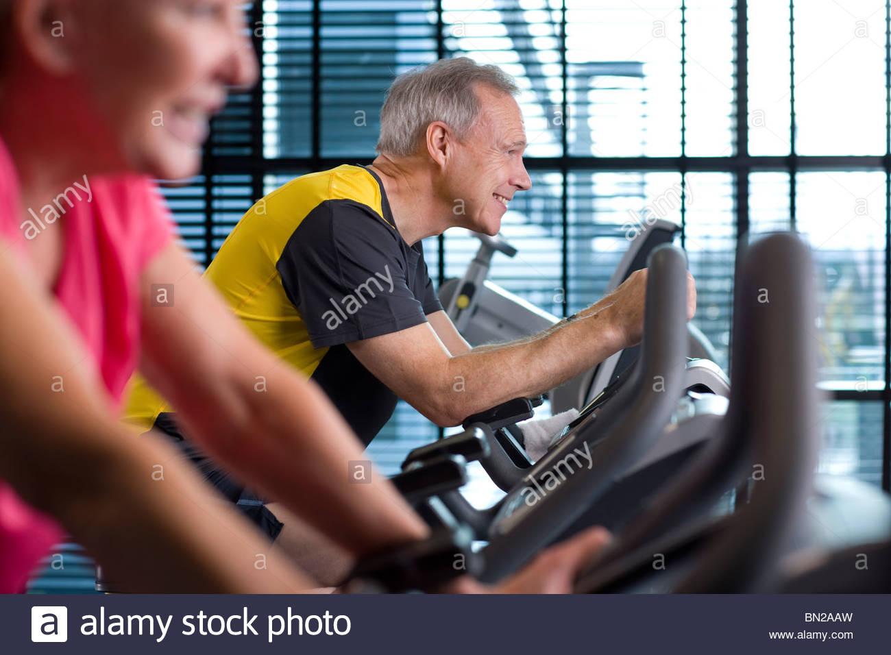Lächelnder Mann Reiten Heimtrainer im Health club Stockbild