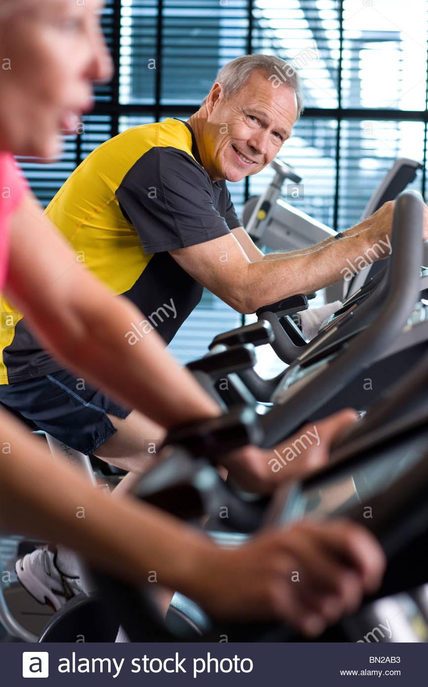 Porträt von lächelnden Mann Reiten Heimtrainer im Health club Stockbild