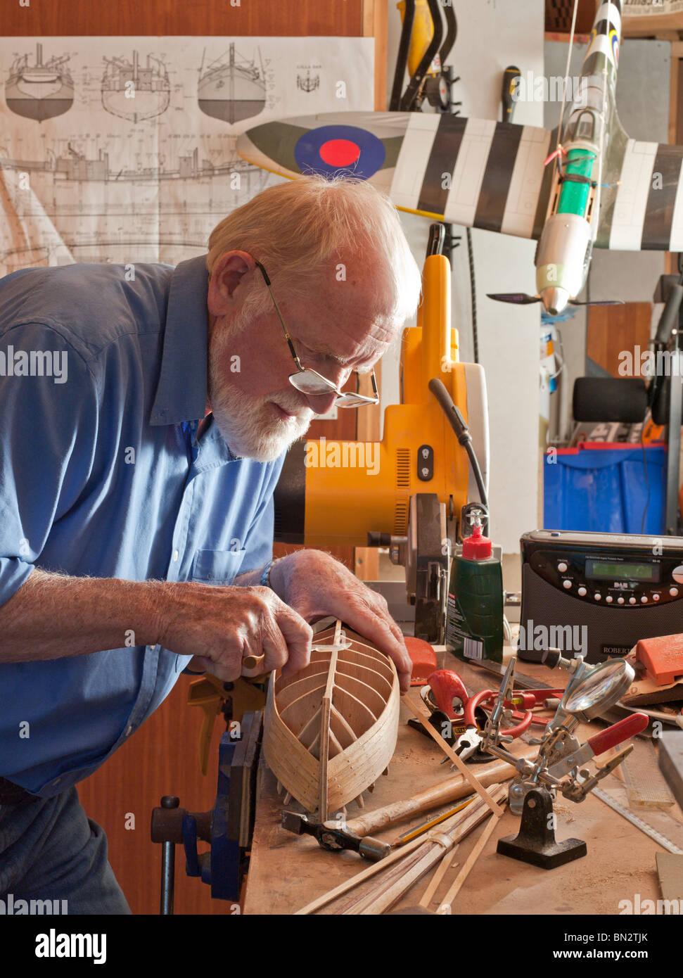 Älterer Mann, Rentner, Modellboot in Werkstatt machen. UK Stockbild