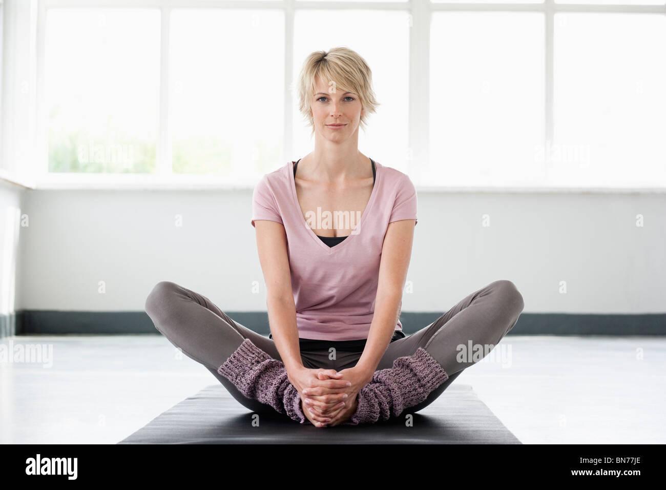 Frau, die Dehnung der Beine auf Yoga-Matte Stockbild