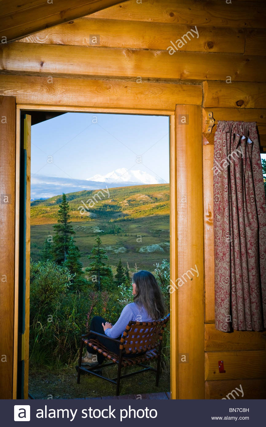 Gast entspannt ihre Außenkabine & genießt die Aussicht an Camp Denali Lodge, Denali-Nationalpark, Stockbild
