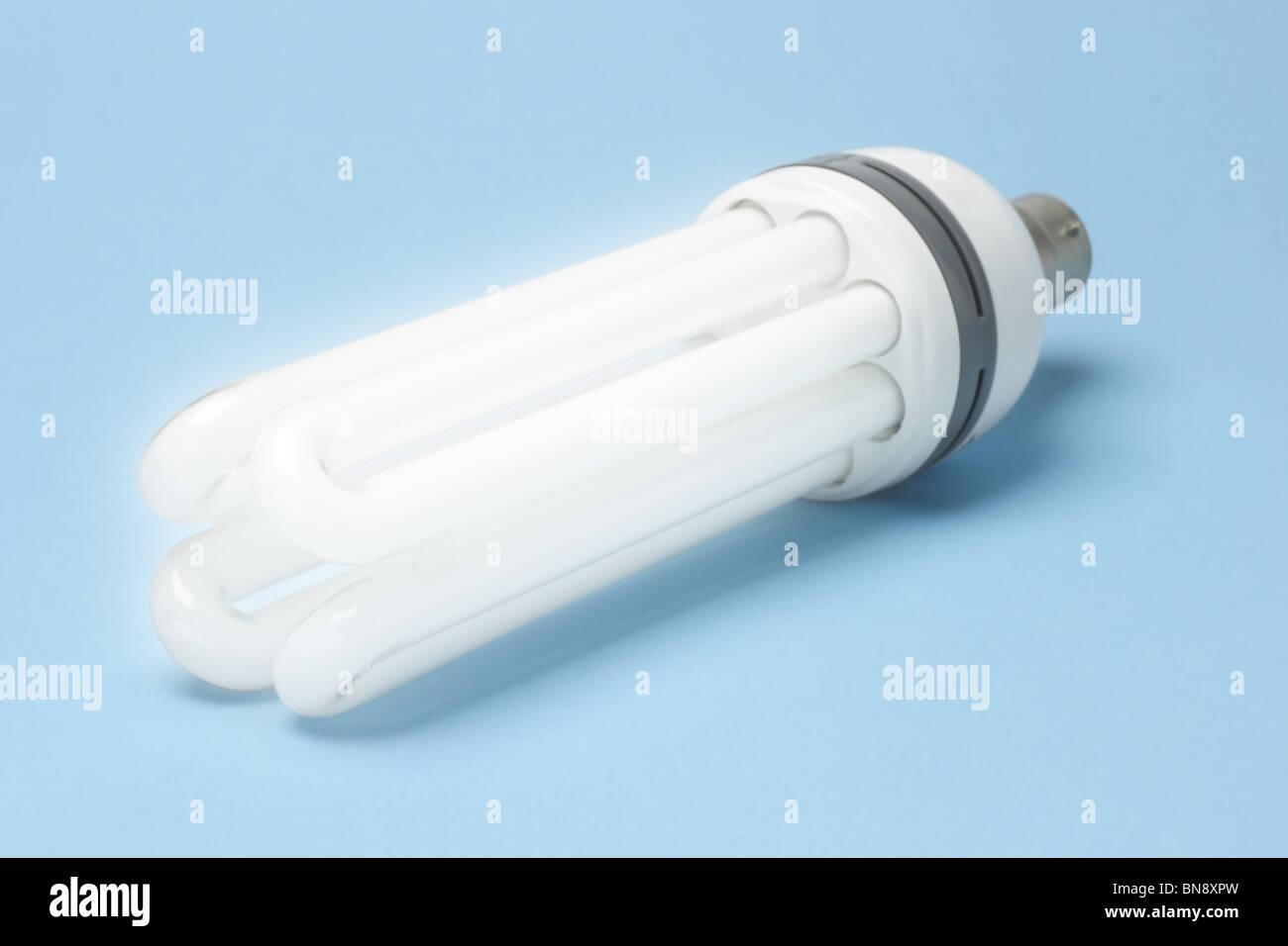 Tageslicht Energie effiziente Leuchtstoff Glühlampe auf blauem Hintergrund Stockbild