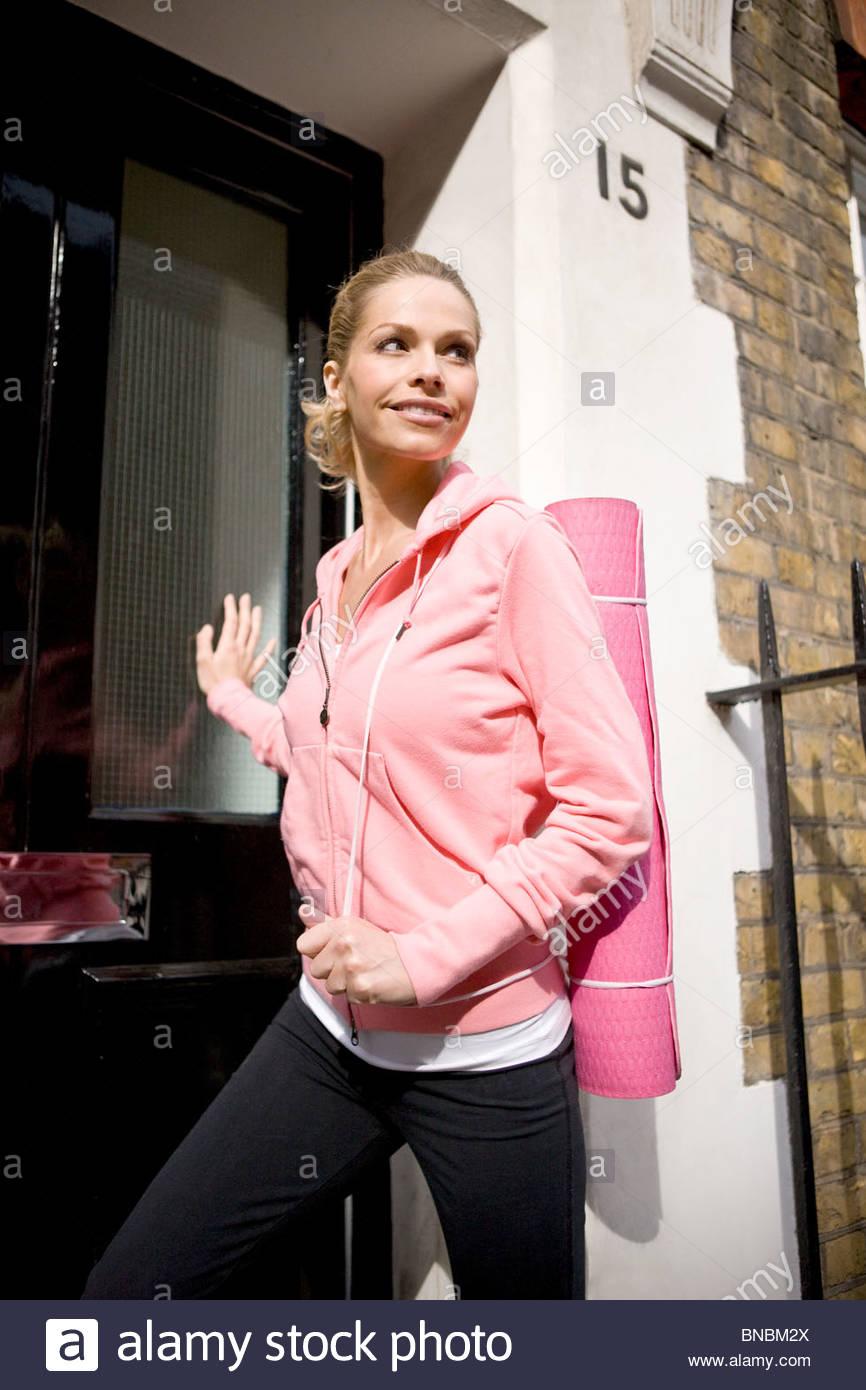 Ein Mitte Erwachsene Frau verlassen ihr Haus trägt eine Yoga-Matte Stockbild