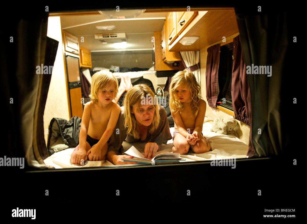 Mutter, lesen eine Gutenachtgeschichte für ihre Kinder in einem RV-Wohnmobil in Texas, USA Stockfoto