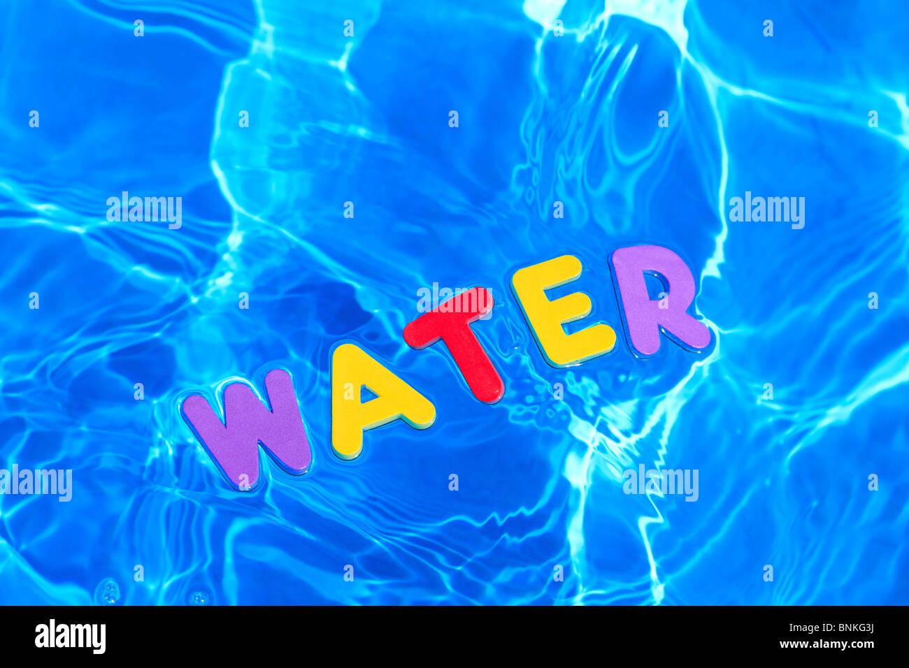 Das Wort wurde Wasser aus Schaum schwimmt auf der Wasseroberfläche eines Schwimmbades Stockbild