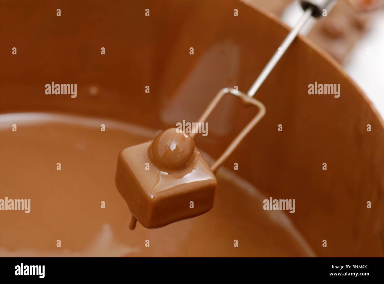 Pralinen Herstellung, leere wird in Schokolade getaucht. Stockbild