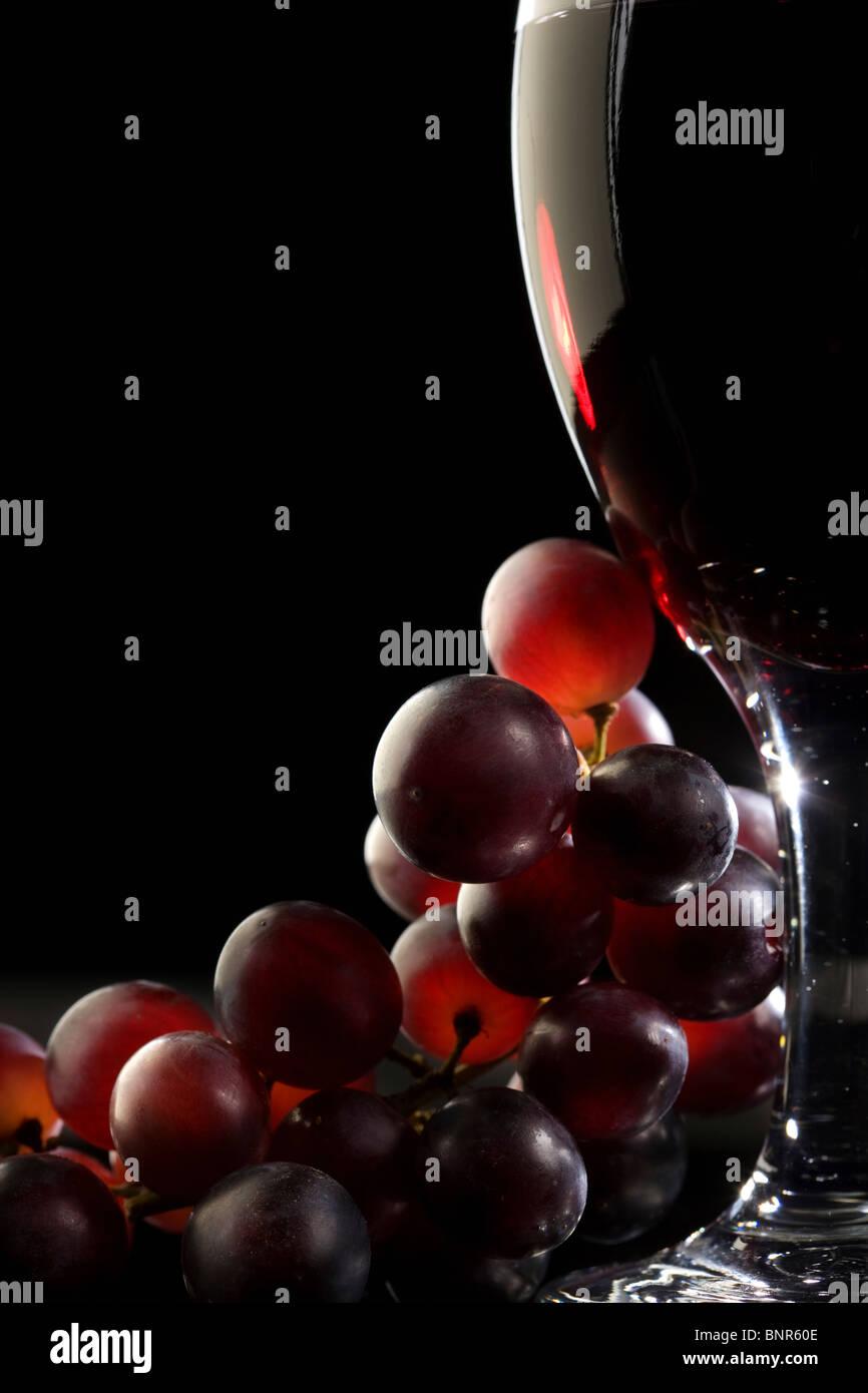 Nahaufnahme von roten Trauben und einem Glas Rotwein Stockbild