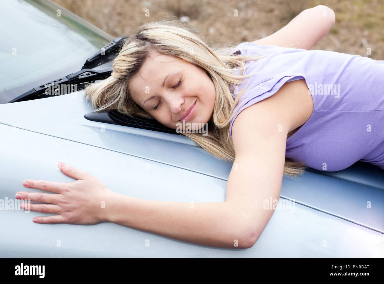 Fröhliche Fahrerin umarmende ihr neues Auto Stockfoto