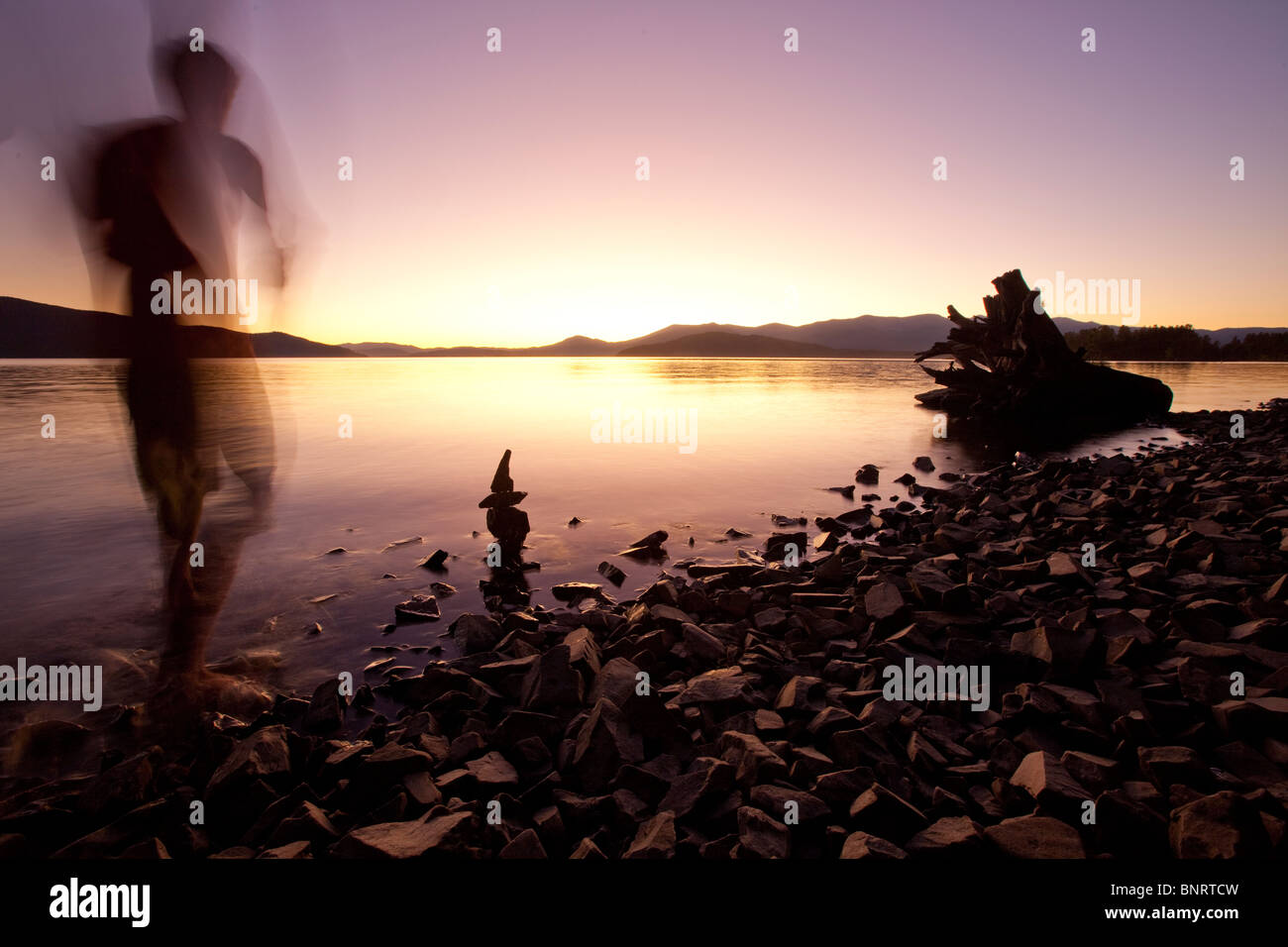 Eine männliche Figur, Sonnenuntergang über einem See und die Berge in Idaho. Stockbild