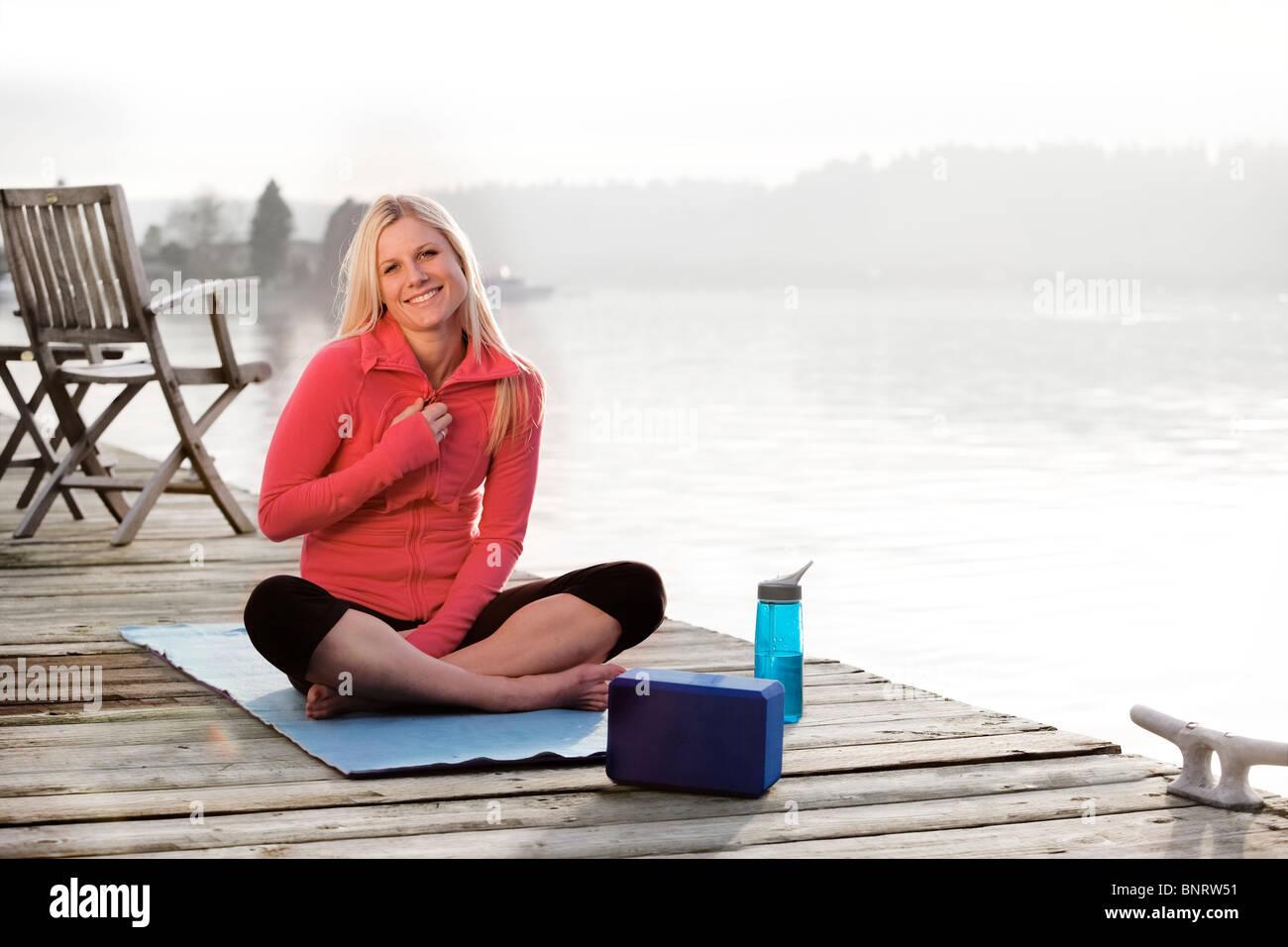 Eine junge Frau hanging out an einem Dock über Lake Washington und lächelnd in die Kamera während Stockbild