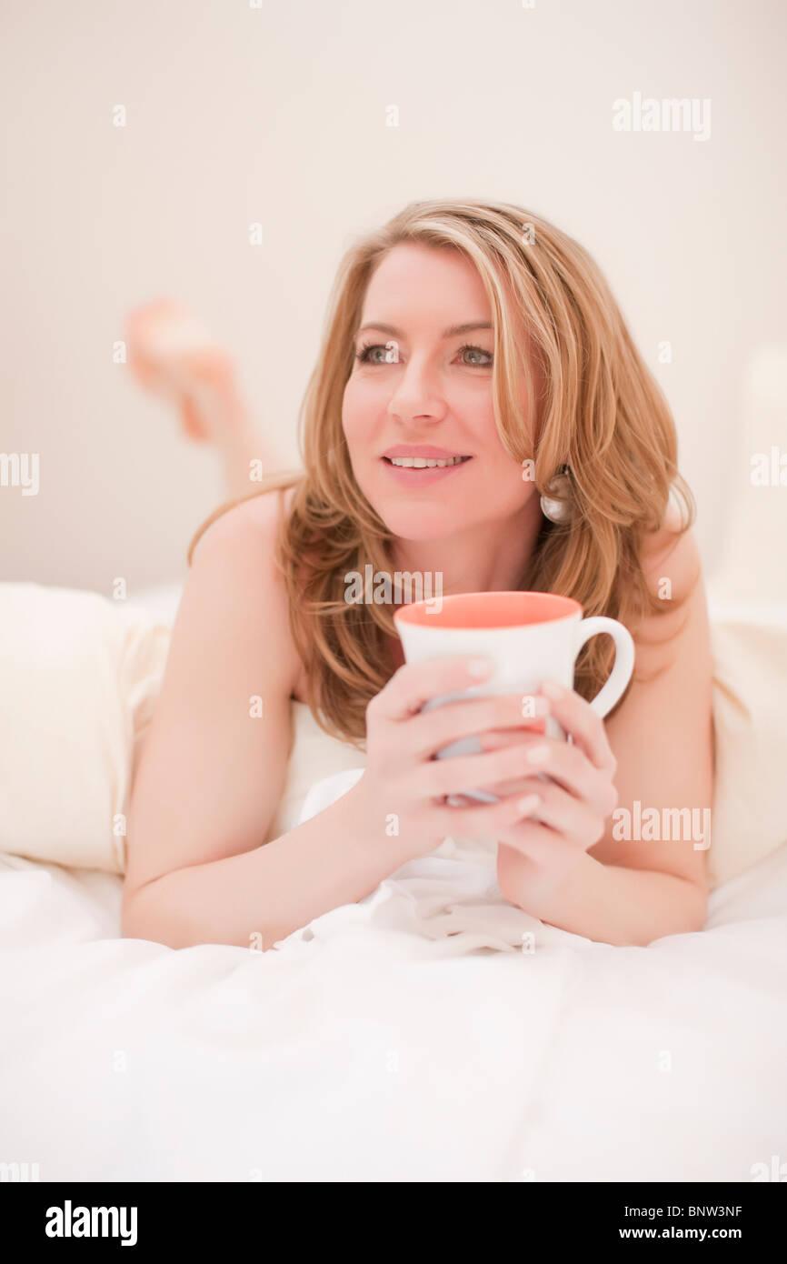 Frau liegend mit einer Tasse Kaffee Stockbild