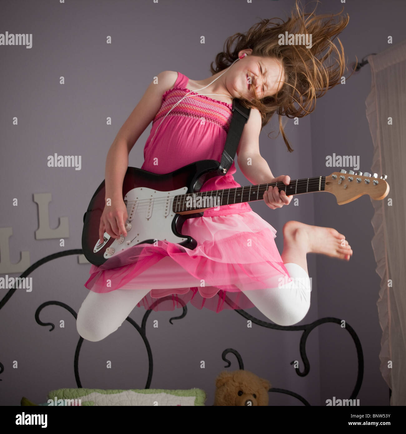 Junge Mädchen, die Gitarre zu spielen, auf ihrem Bett Stockfoto