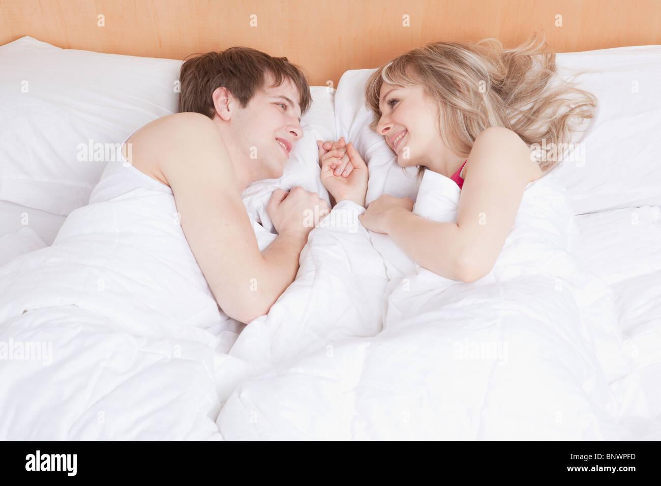 Paar im Bett liegend zusammen Stockbild