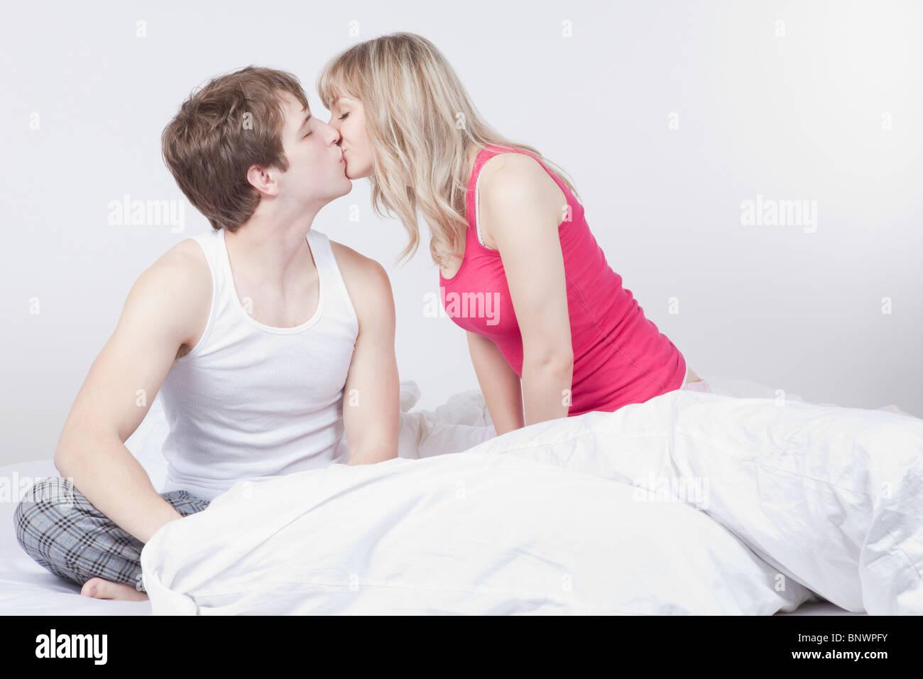 Paar Küssen auf Bett Stockbild