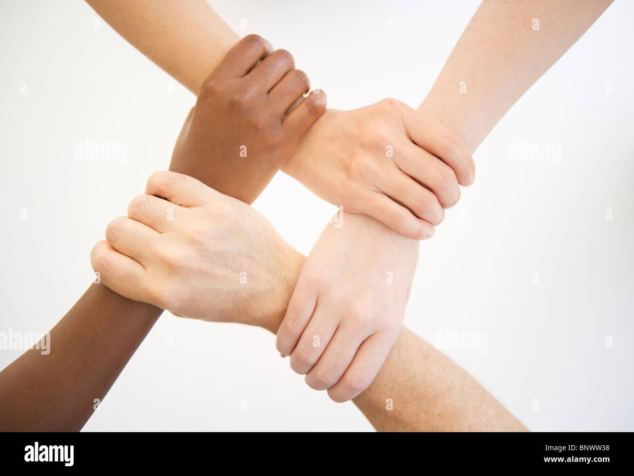Vier Hände halten Handgelenke anderer Menschen Stockbild