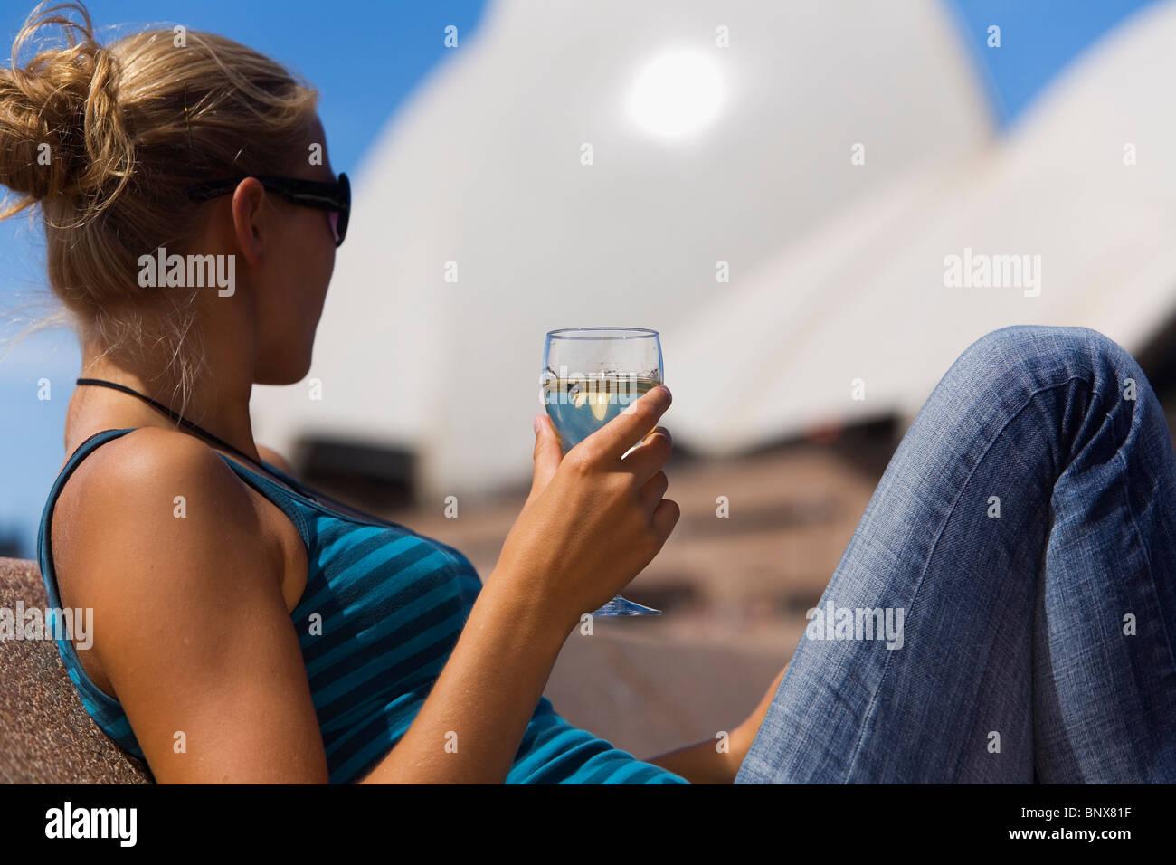 Eine Frau genießt ein Glas Wein in der Opera Bar mit der Oper im Hintergrund.  Sydney, New South Wales, Australien. Stockbild
