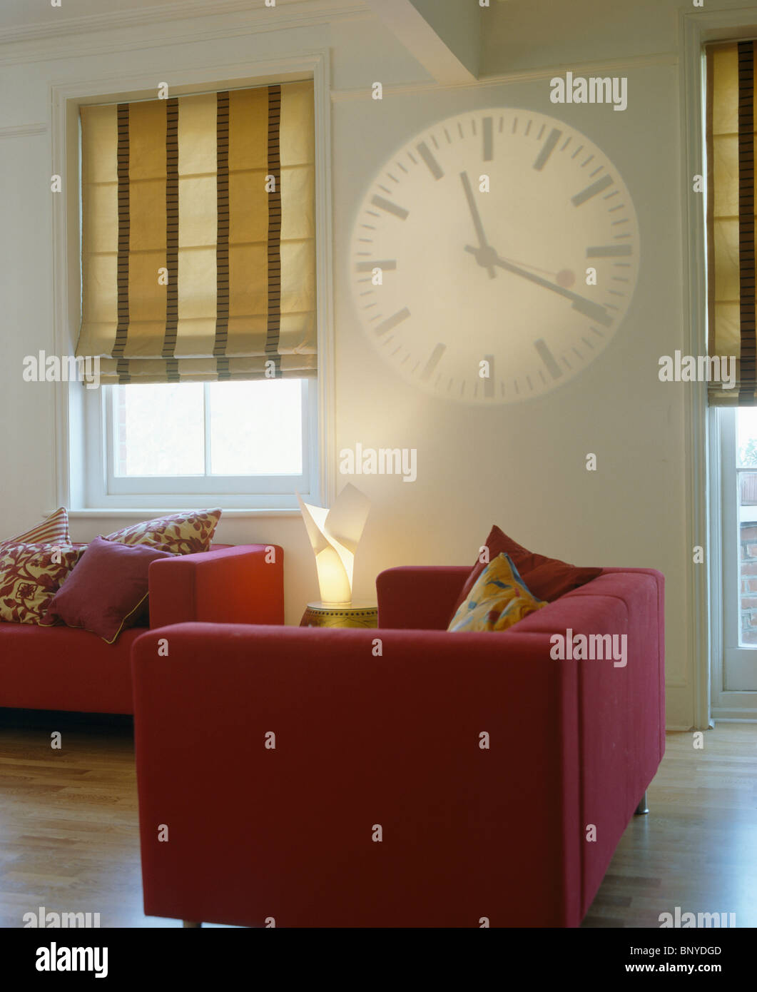 GroB Hologramm Uhr An Wand Neben Fenster Breit Gestreift Beige Jalousien Inn  Moderne Weiße Wohnzimmer Mit Roten Sofas