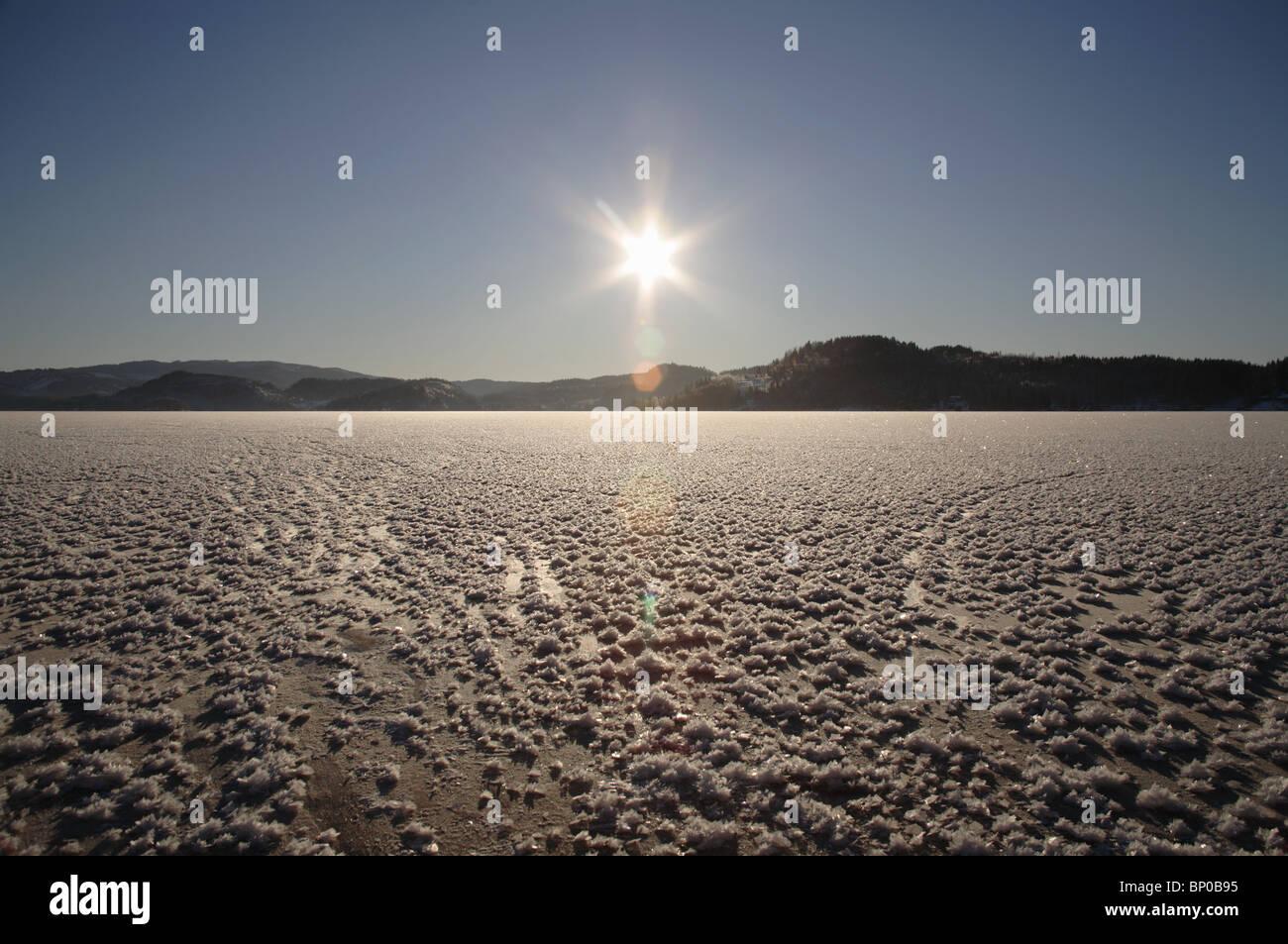 Zugefrorenen See, Sonne tief am Horizont Stockbild
