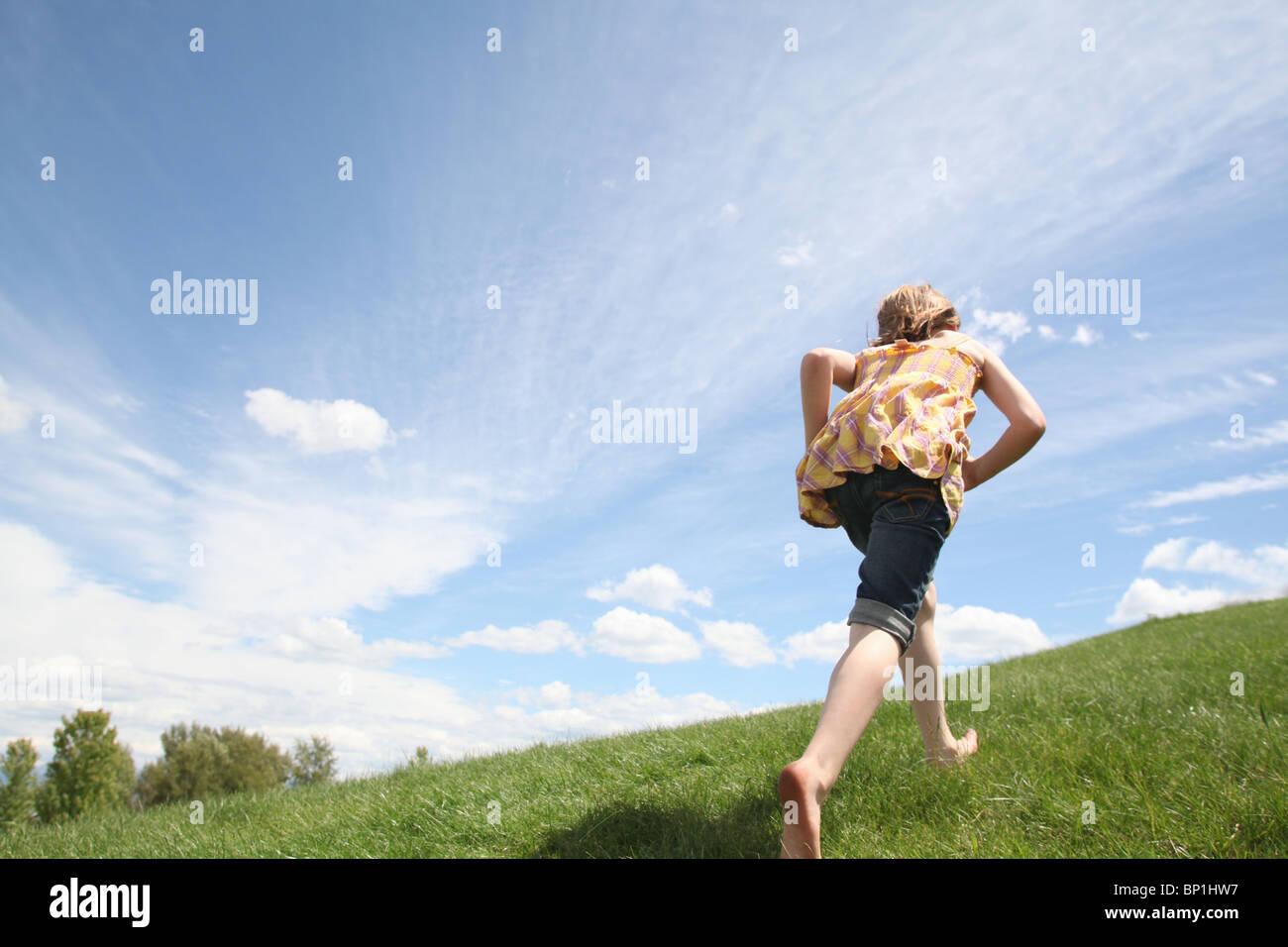 junge Mädchen Wiesen bergauf laufen Stockbild
