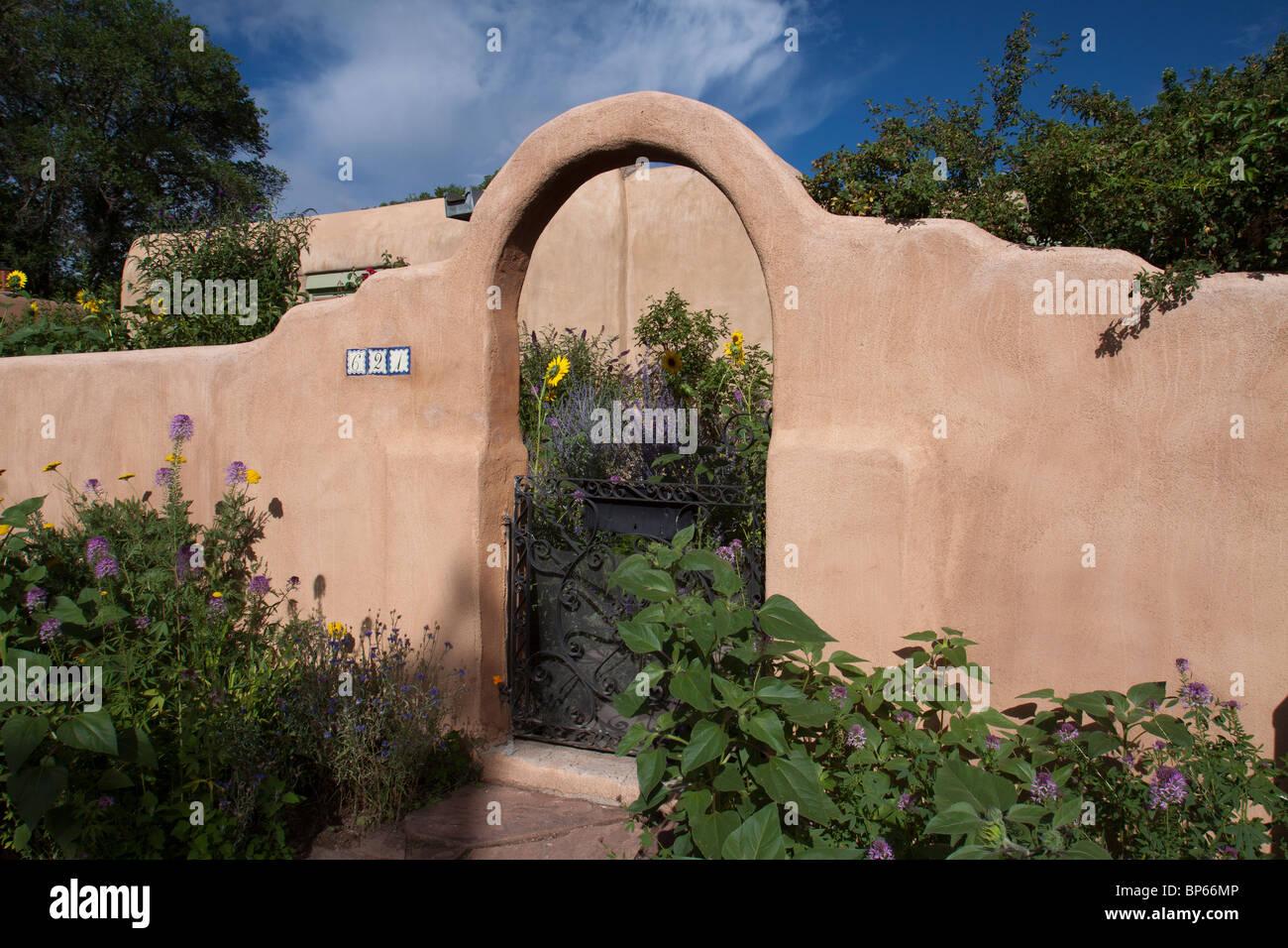 Haus mit Adobe Mäuerchen mit gewölbte Eingangstor in Pueblo-Revival-Stil-Architektur des Südwestens Stockbild
