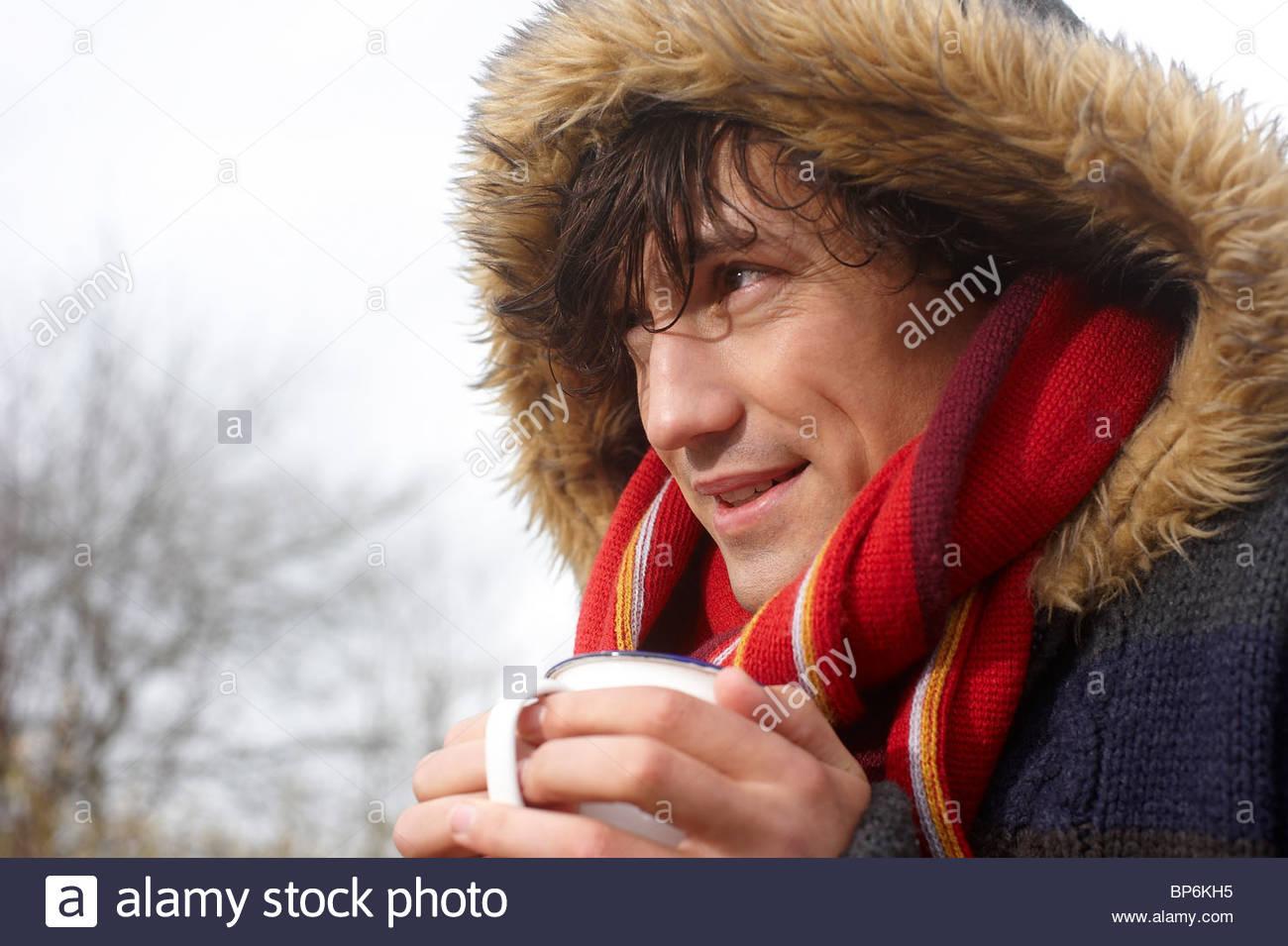 Ein reifer Mann stehend im Freien im Winter halten Sie ein heißes Getränk Stockbild