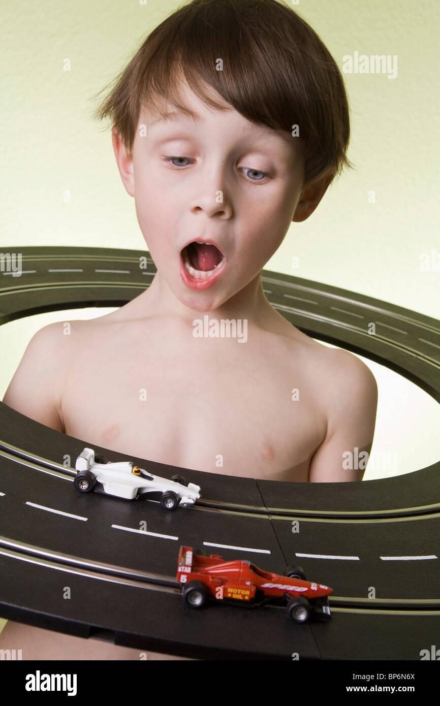Ein Junge in der Mitte einer Spielzeug-Rennbahn beobachten das Spielzeug Rennwagen Rennen Stockbild
