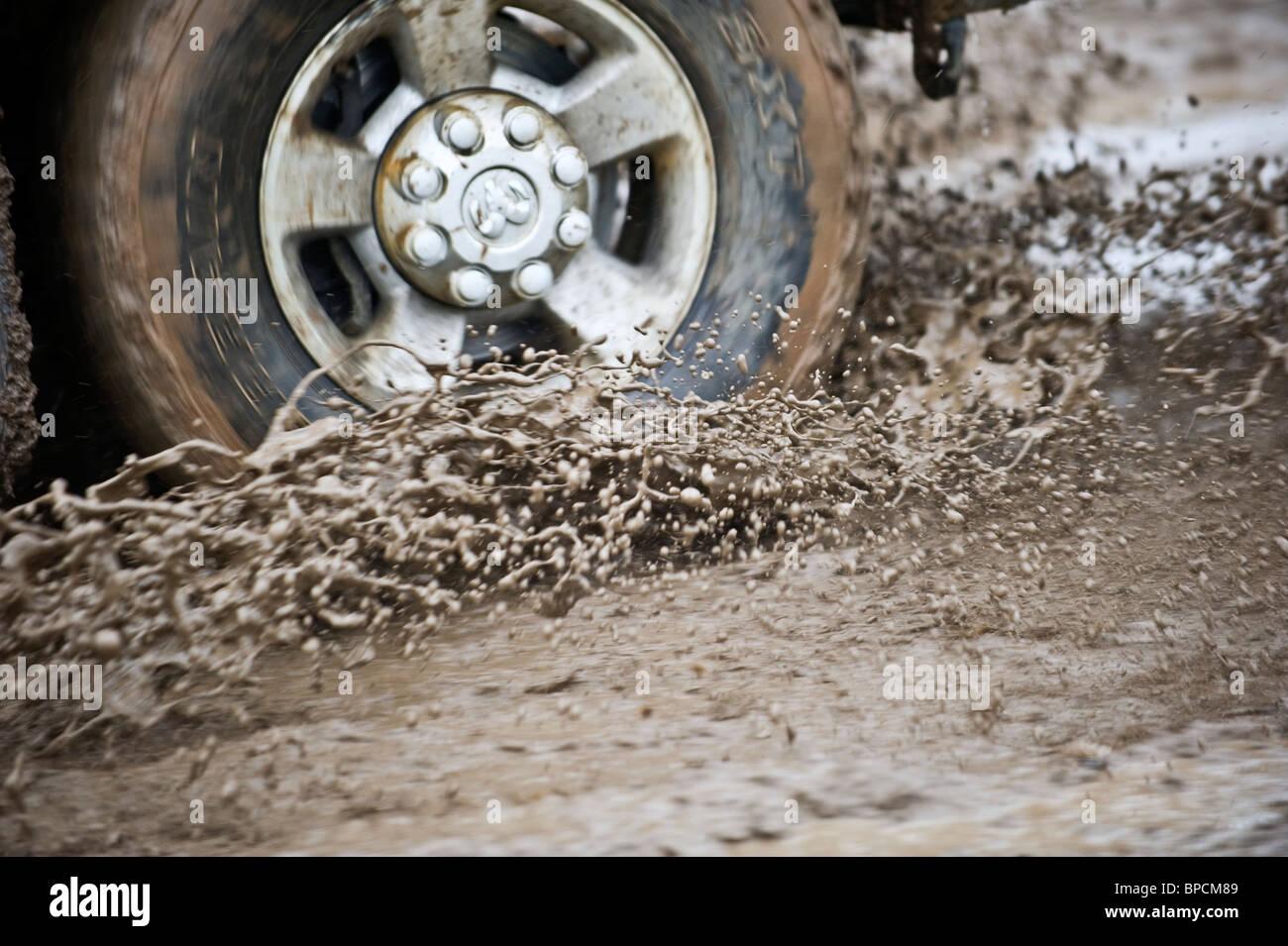 Ein Bild von einem LKW-Reifen und Rad dreht durch ein Schlammloch. Stockbild