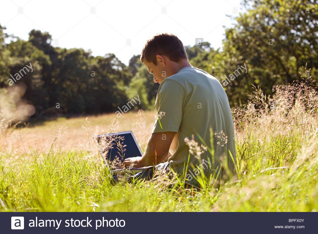 Ein junger Mann sitzt auf dem Rasen mit einem laptop Stockbild