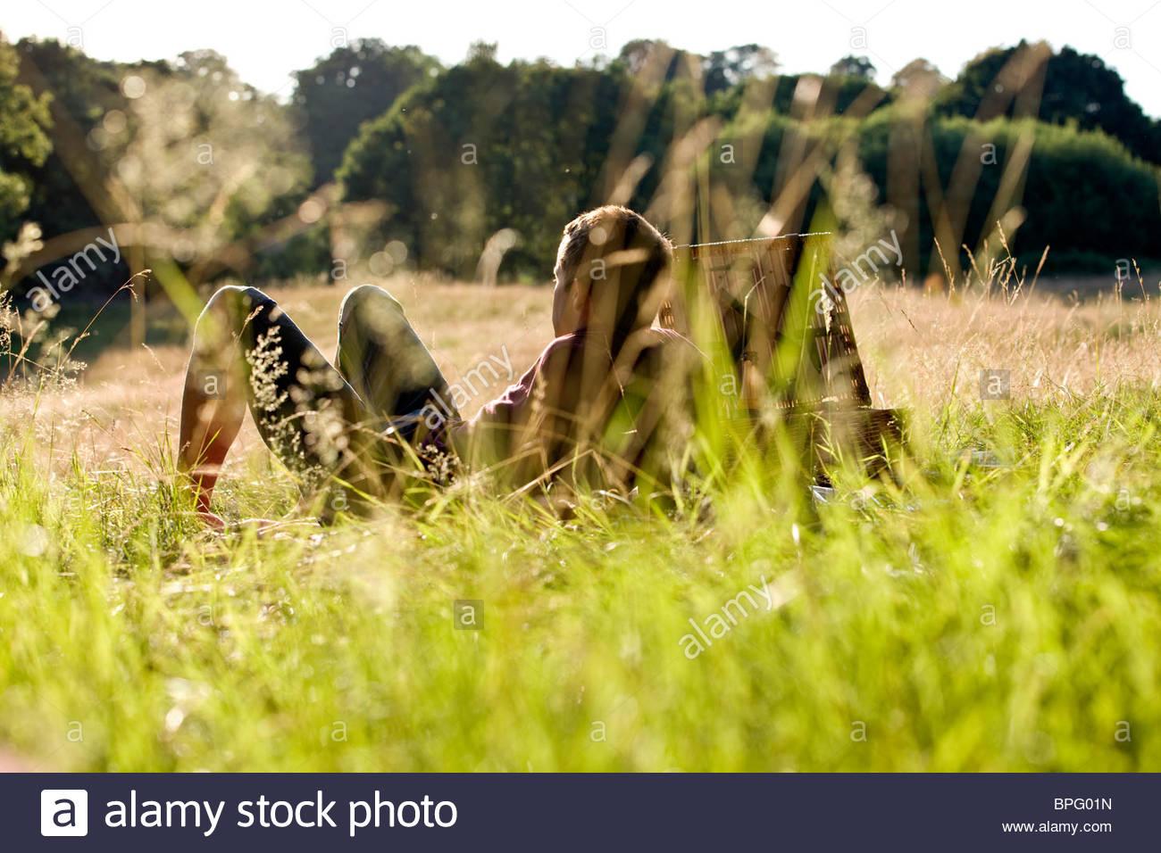 Ein junger Mann sitzt auf dem Rasen, die Sonne genießen Stockbild