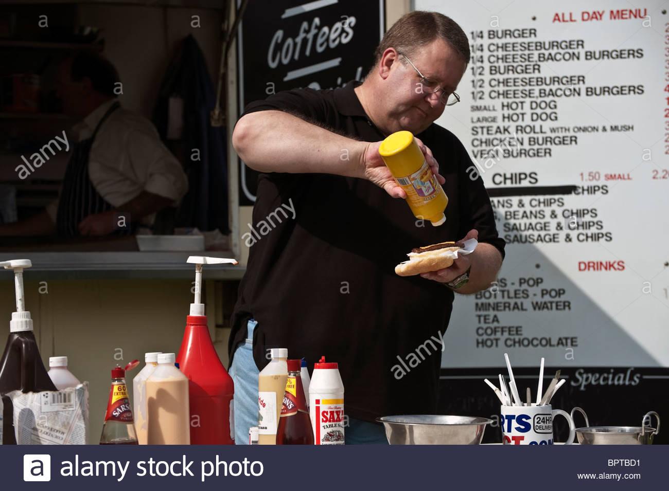 Dicker Mann Essen Junk-Food zu einem Outdoor-catering van, UK. Übergewichtige Menschen draußen einen Burger Stockbild
