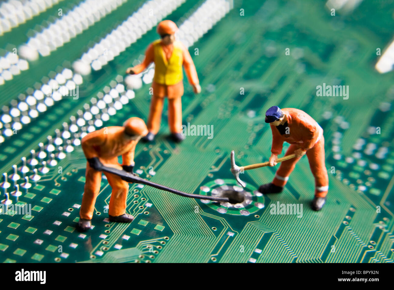 Arbeiter-Figuren auf eine Computer-Platine platziert Stockbild