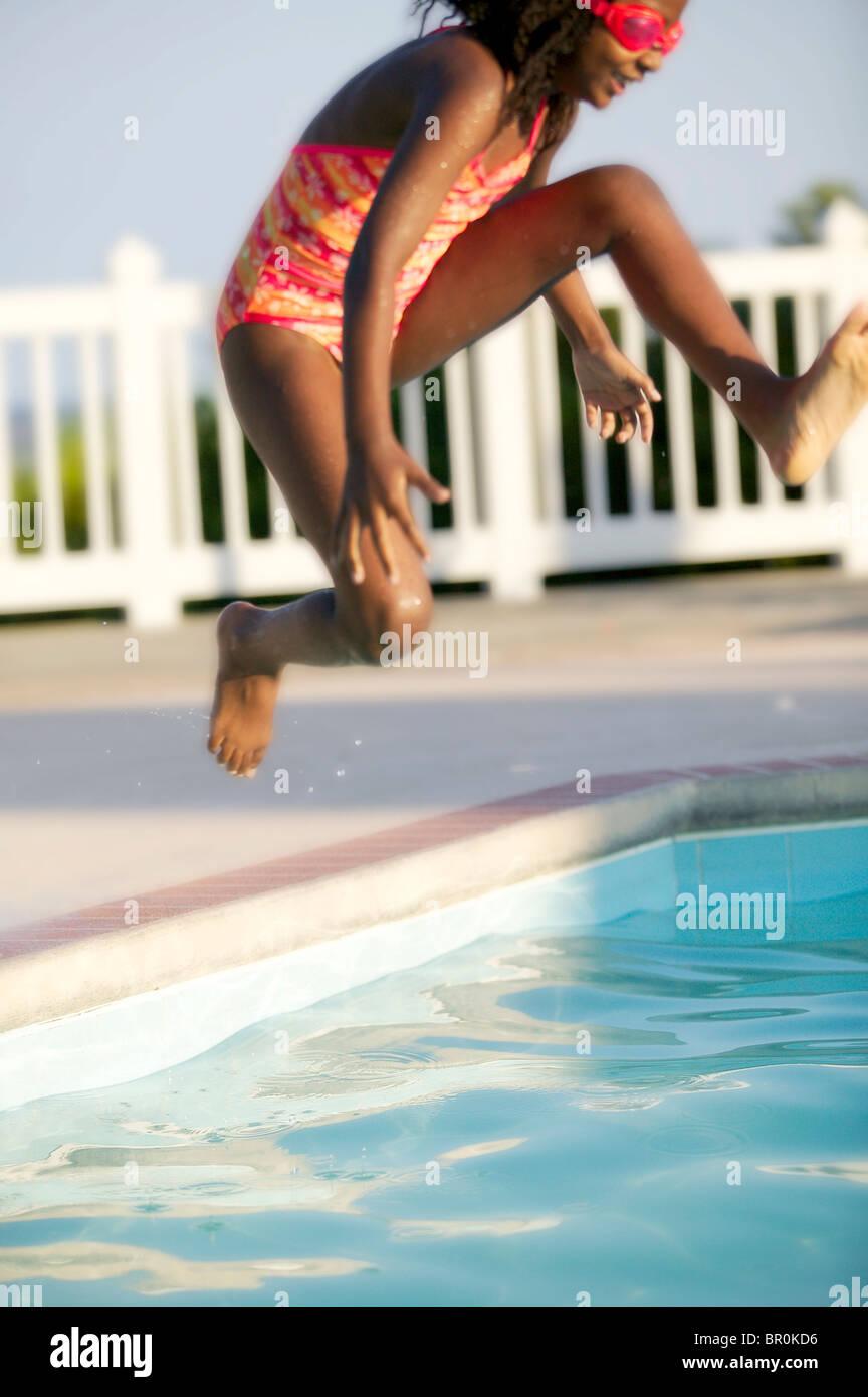 Afroamerikanische Mädchen springen in einen Swimmingpool. Stockfoto