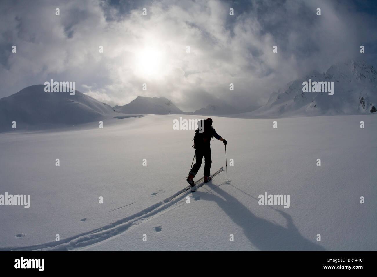 Backcountry Skifahrer kreuzt Gletscher unter Gewitterhimmel späten Tag. Stockfoto